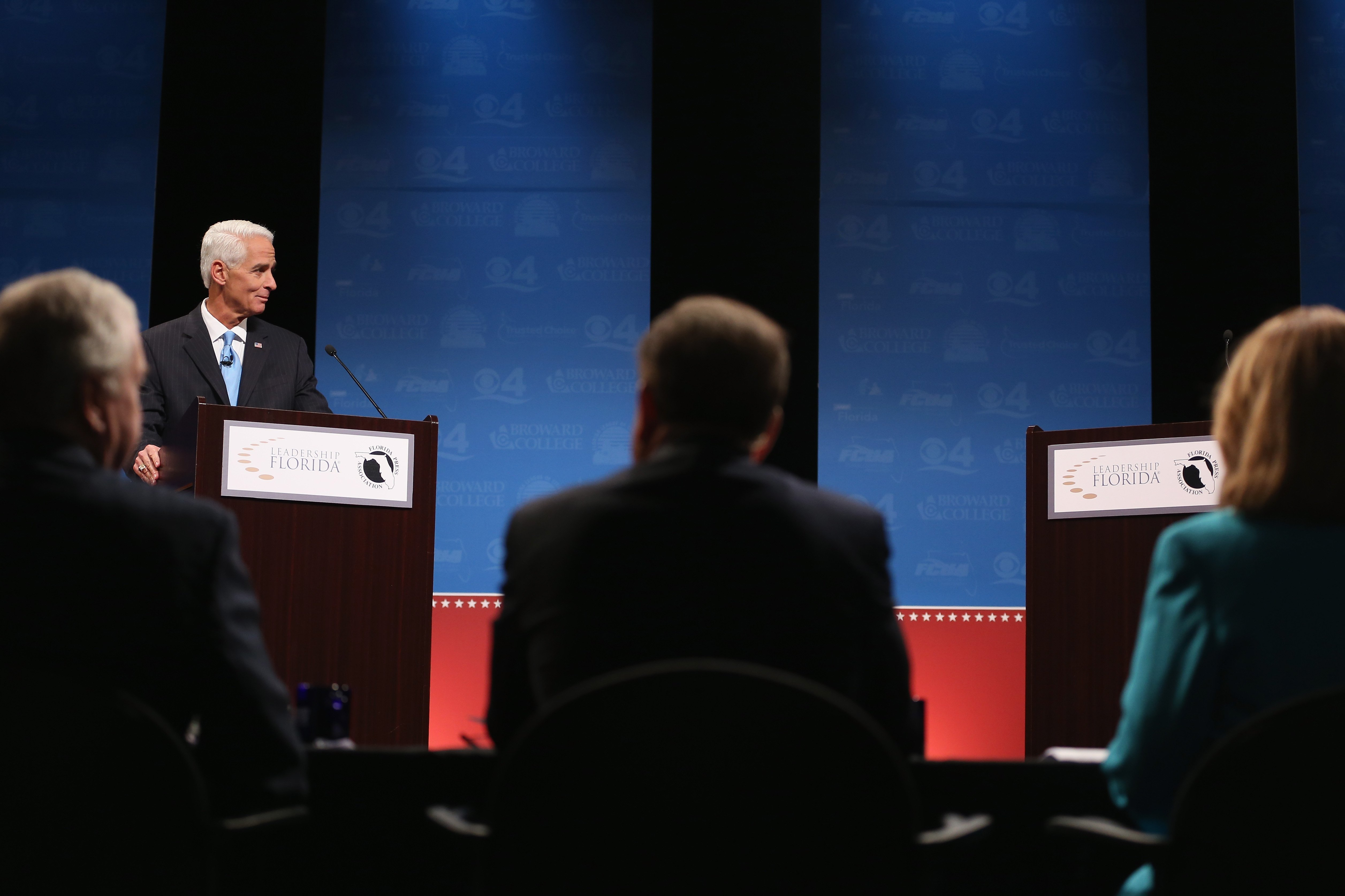 Former Florida Governor and Democratic candidate for Governor Charlie Crist waits next to an empty podium for Republican Florida Governor Rick Scott who delayed his entry onto the stage due to an electric fan that Crist had at his podium at a televised debate at Broward College on Oct. 15, 2014 in Davie, Florida.