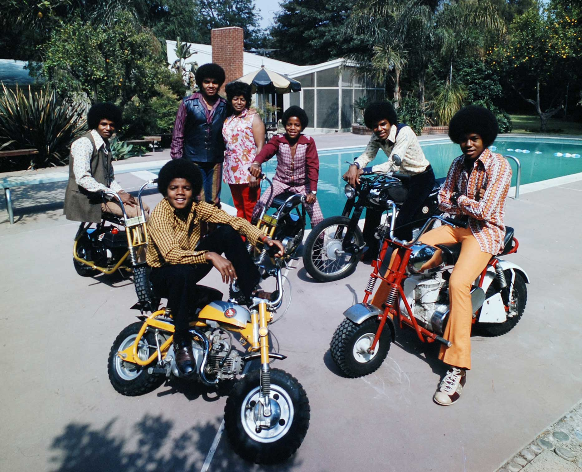 With their parents standing by, 13-year-old dynamo Michael (front left) and his brothers Jackie, Marlon, Tito and Jermaine straddle their motorbikes by the pool, 1970.