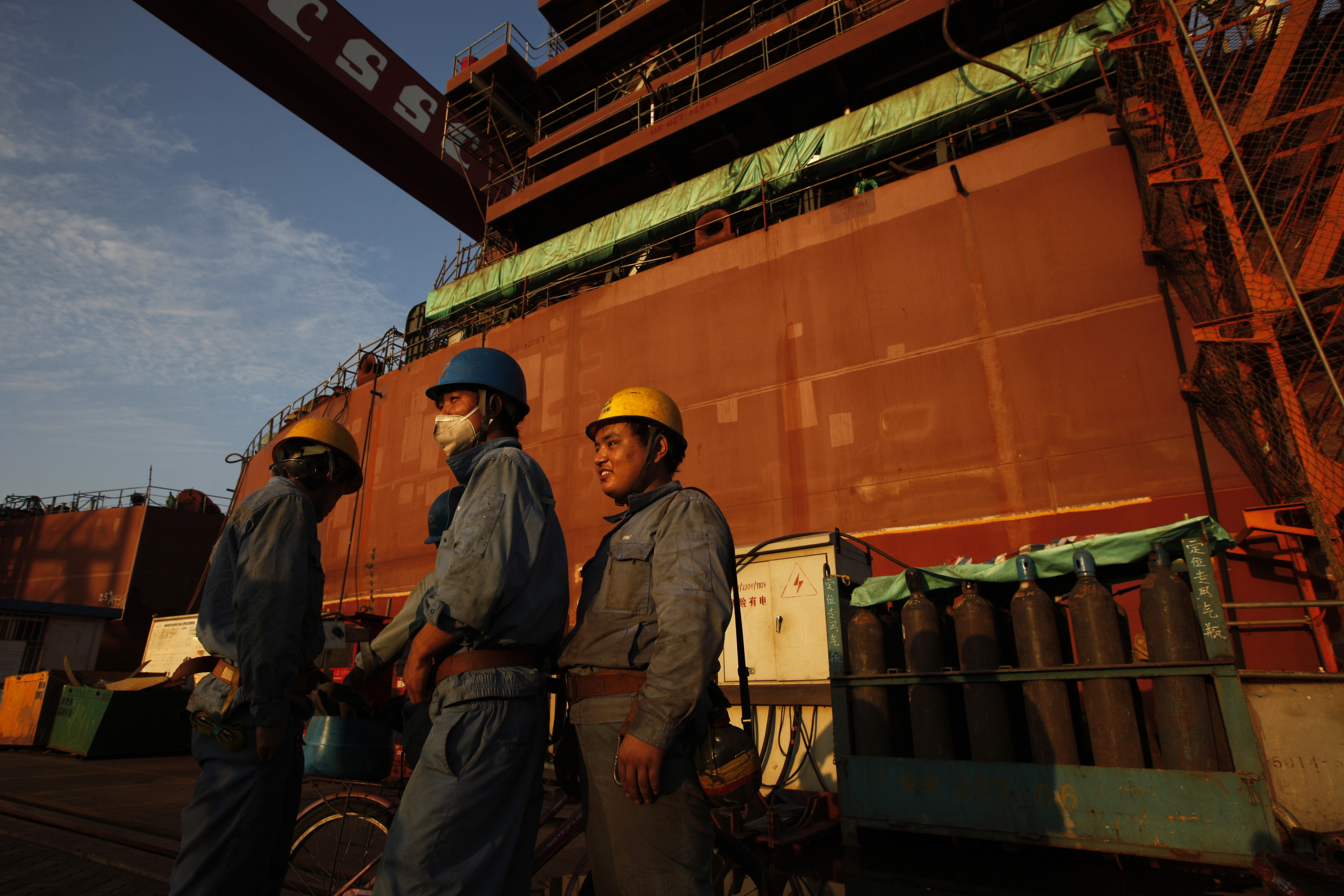 Employees stand in front of nearly completed ship at China State Shipbuilding Corporation (CSSC) Longxue shipbuilding, in the southern Chinese city of Guangzhou November 13, 2011.