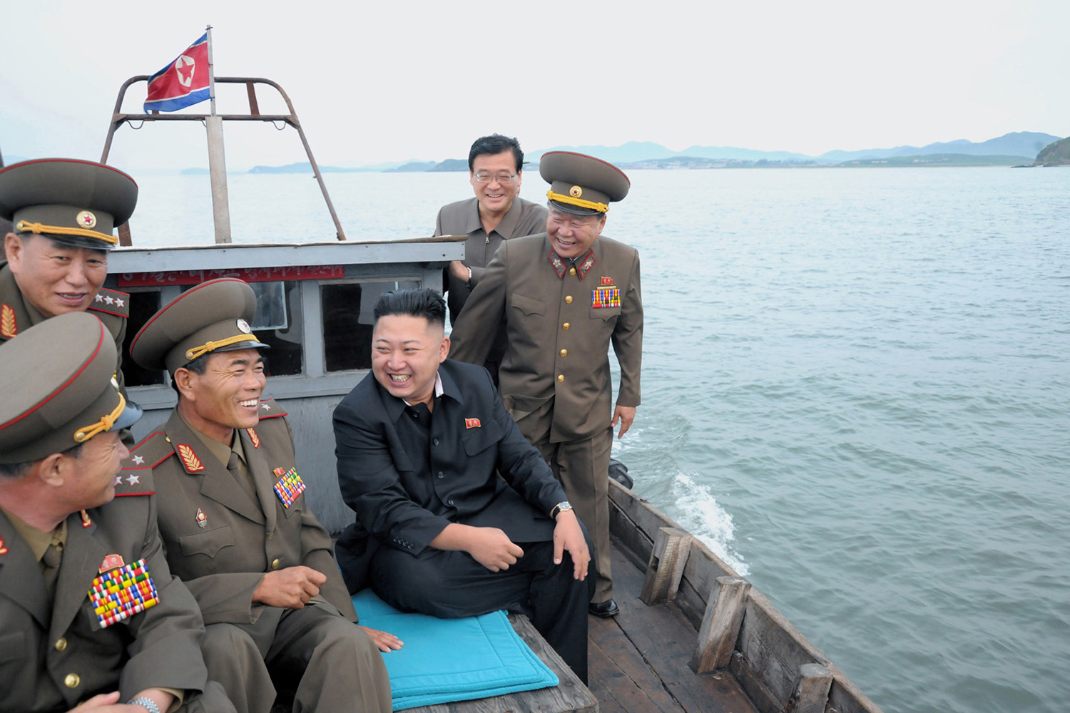 North Korean leader Kim Jong-Un (C) sits in a wooden boat with other soldiers as he visits military units on islands in the most southwest of Pyongyang in this picture released by the North's official KCNA news agency in Pyongyang August 19, 2012.