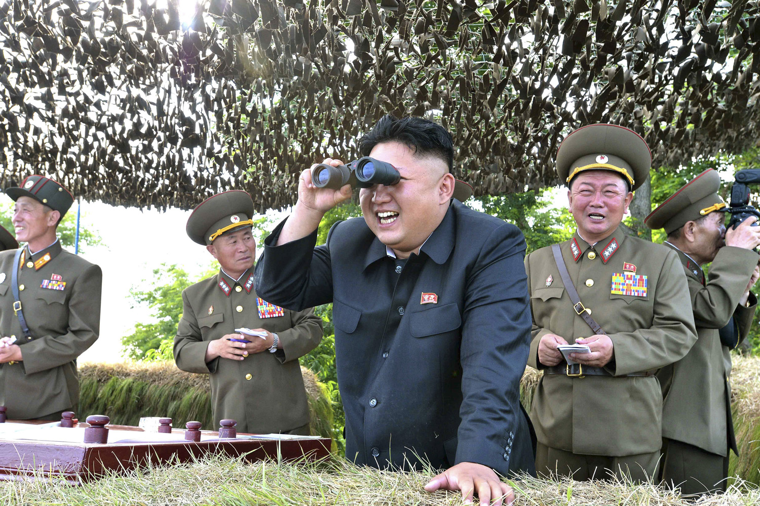 North Korean leader Kim Jong Un looks through a pair of binoculars during an inspection of the Hwa Islet Defence Detachment standing guard over a forward post off the east coast of the Korean peninsula, in this undated photo released by North Korea's Korean Central News Agency (KCNA) in Pyongyang on July 1, 2014.