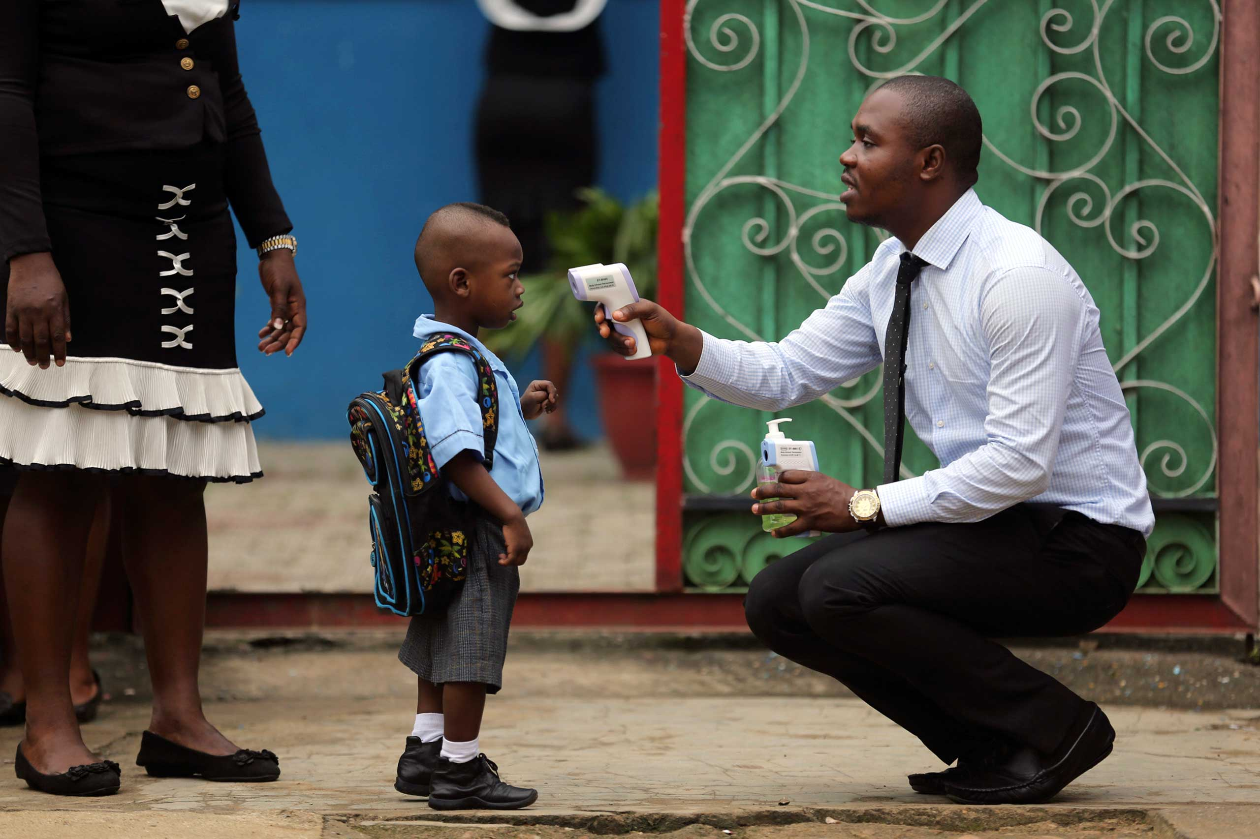 A school official takes a pupil's temperature using an infrared digital laser thermometer in front of the school premises, at the resumption of private schools, in Lagos, Sept. 22, 2014.