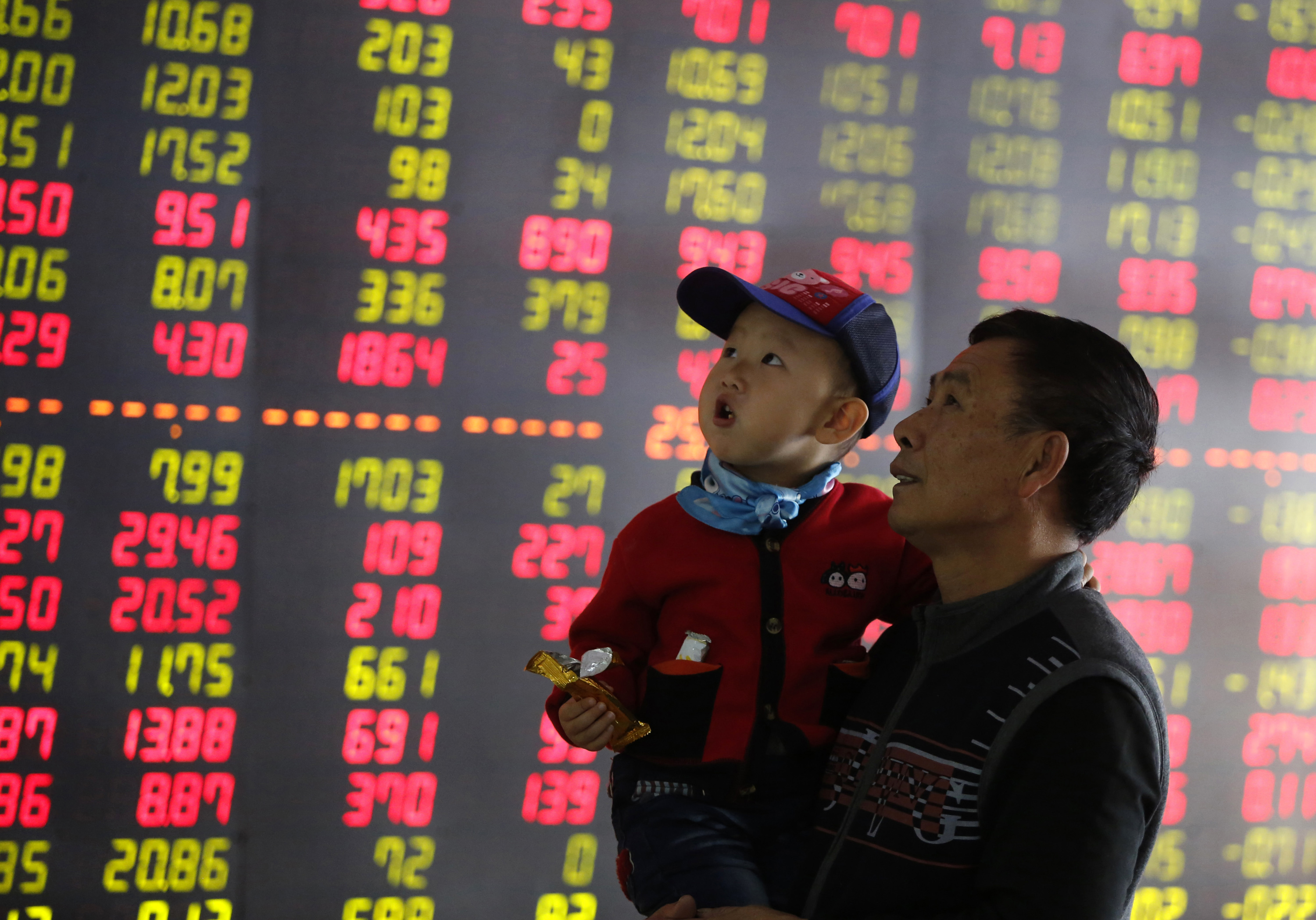 An investor holds a child in front of an electronic screen showing stock information at a brokerage house in Shenyang, Liaoning province, Oct. 16, 2014.