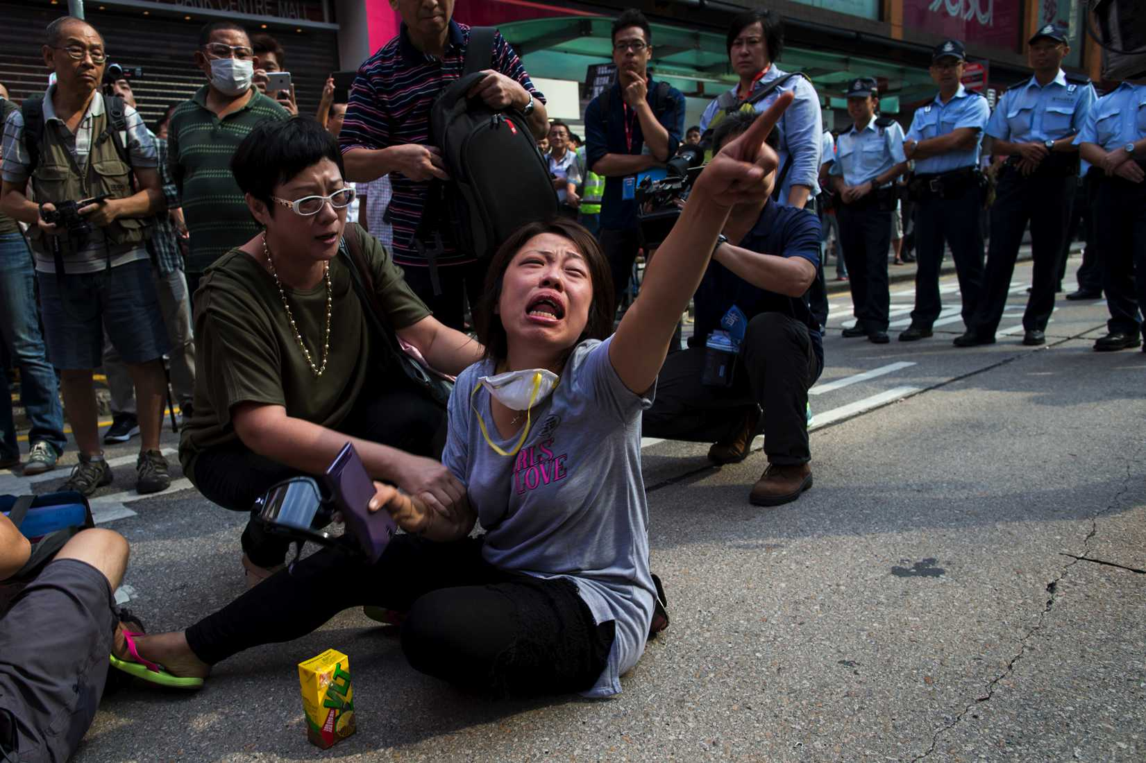 A pro-democracy protester cries in front of a line of policemen on a blocked road, after police removed barricades at Mongkok shopping district in Hong Kong October 17, 2014.