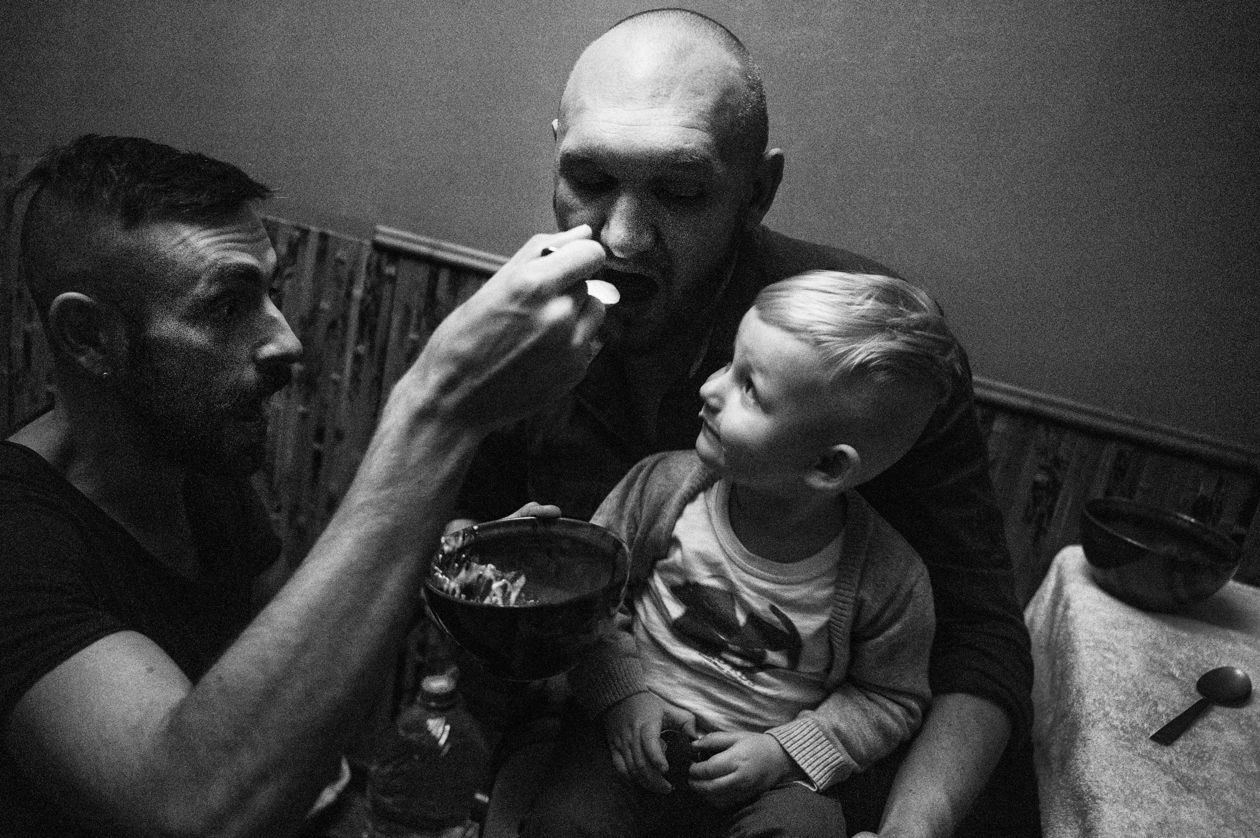Bogdan is feeding Yegor, trying to convince Timur to eat his dinner.
