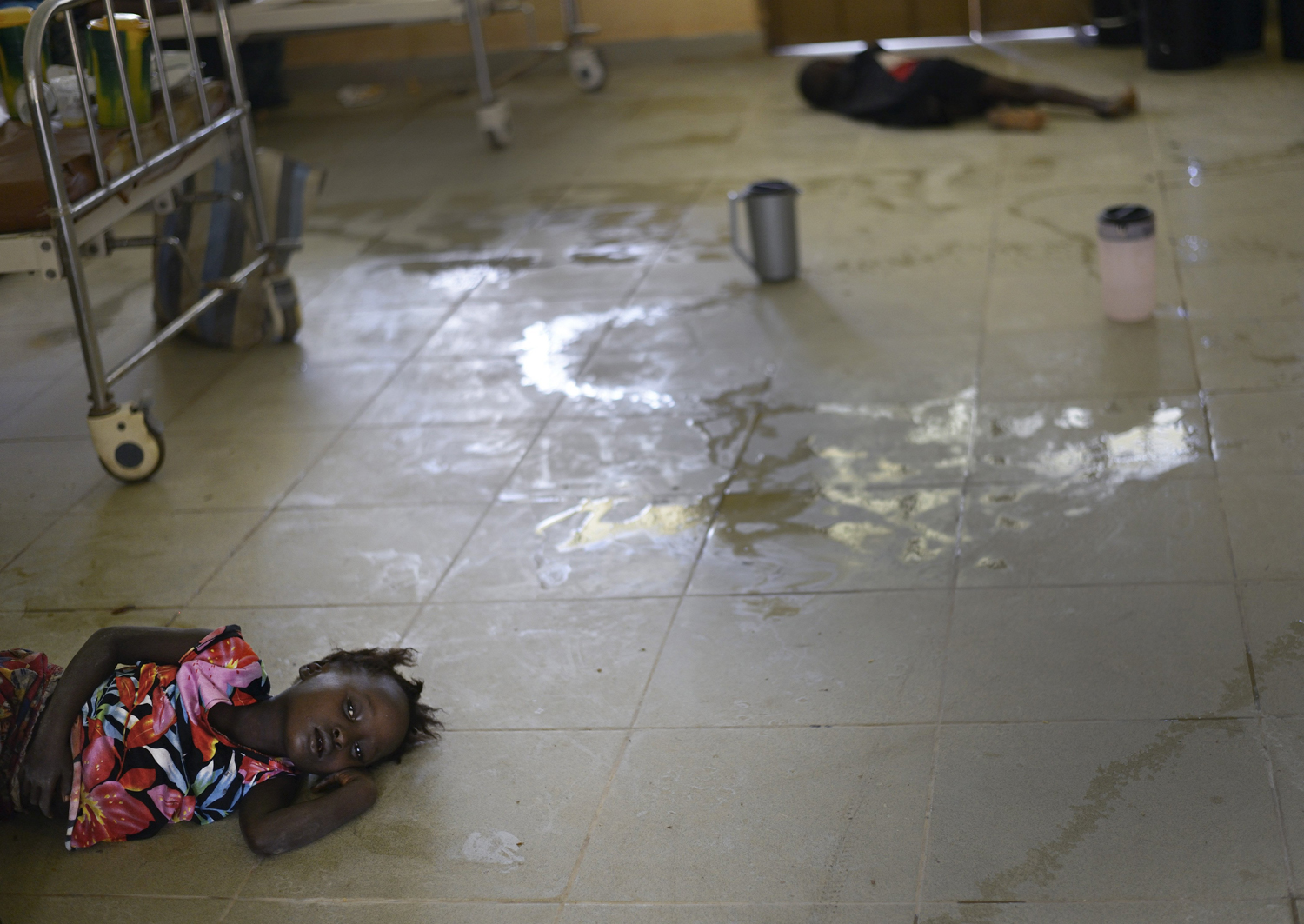 Mariattu Kanu, 4, who is suspected of being infected with Ebola, lies on the floor amid body fluids in a ward for Ebola victims at a hospital in Makeni, Sierra Leone, Sept. 27, 2014.