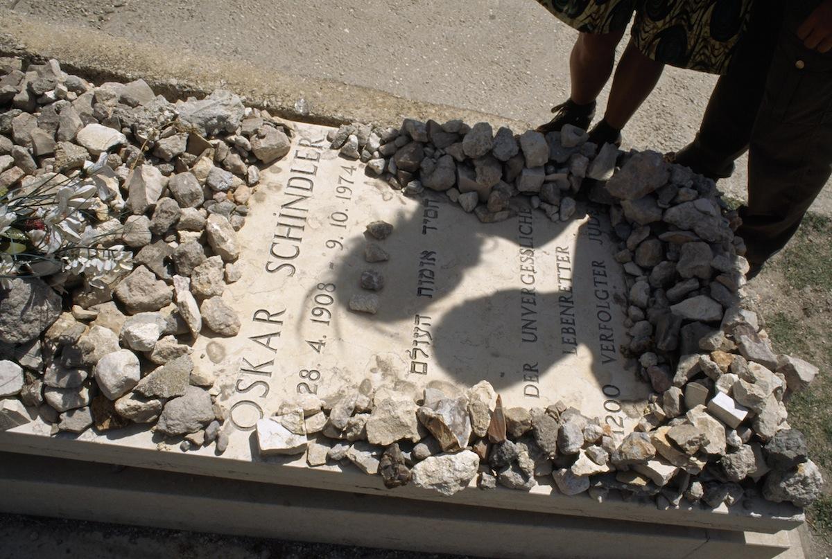 Visitors honor hero Oskar Schindler by placing stones on his grave in Jerusalem