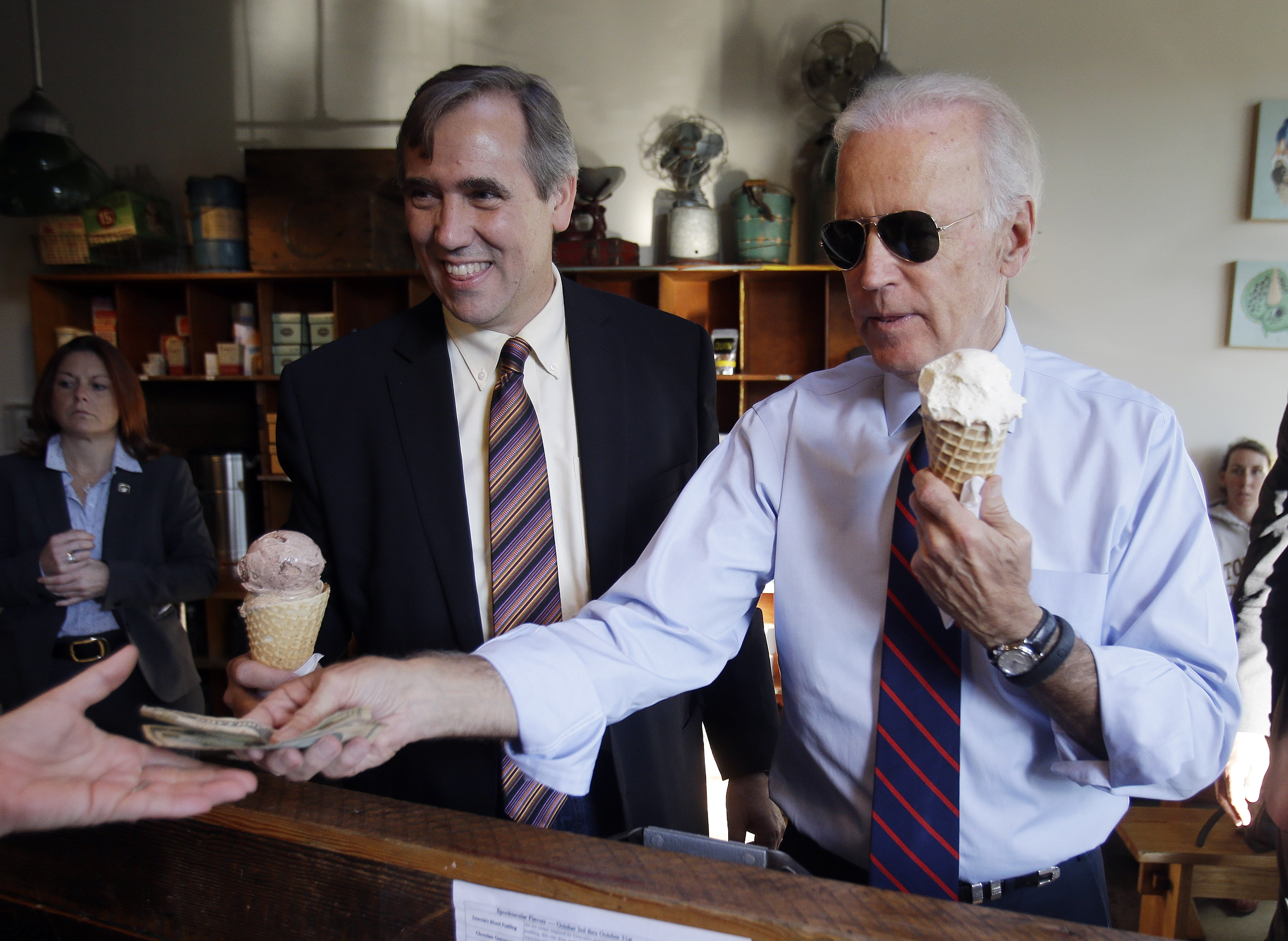 Vice President Joe Biden, right, pays for ice cream cones for himself and U.S. Sen. Jeff Merkley after a campaign rally in Portland, Ore., Wednesday, Oct. 8, 2014.