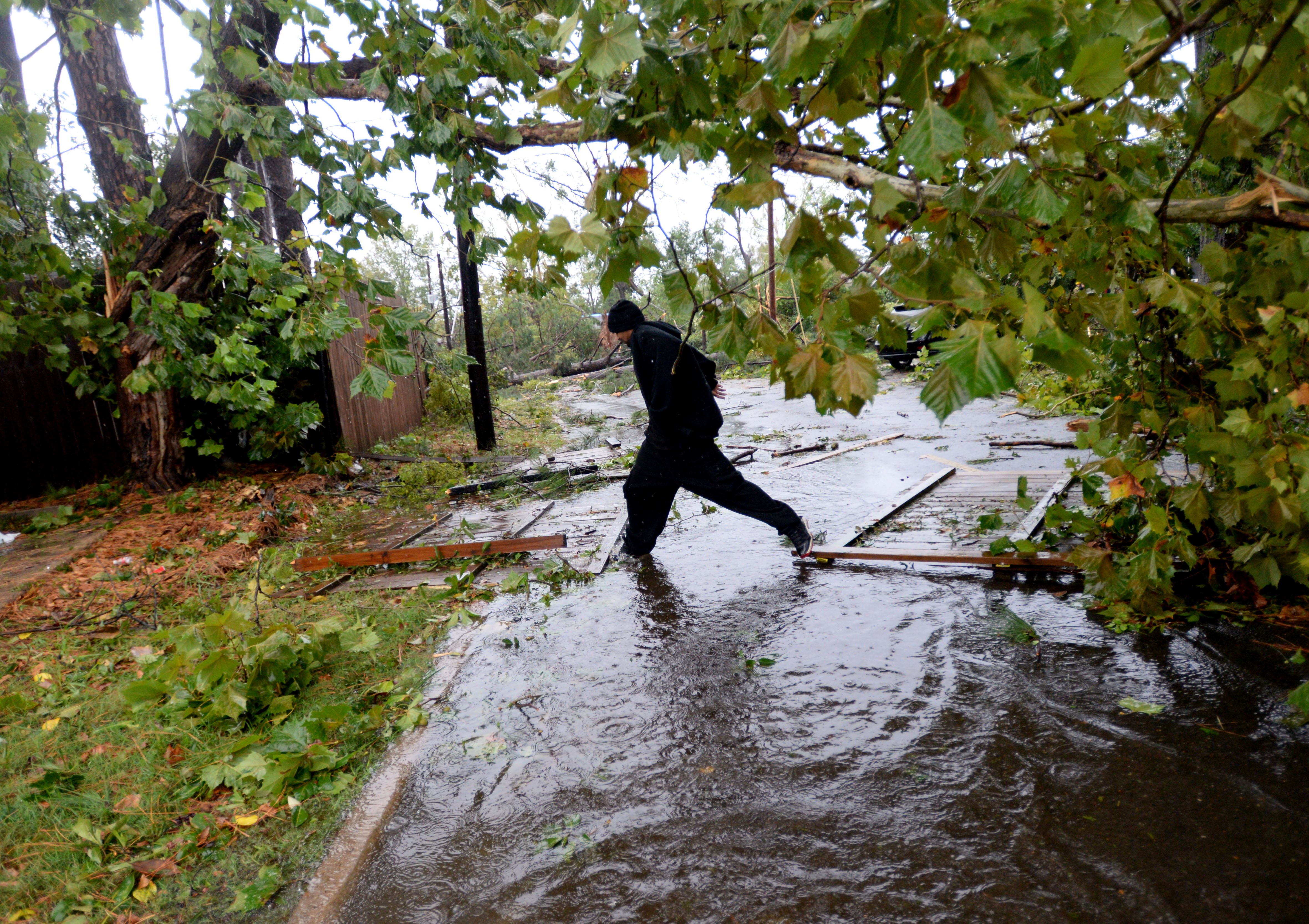 Mike Doyle jumps over a puddle while checking on a house that was damaged in the storm in Monroe, La., on Oct. 13, 2014