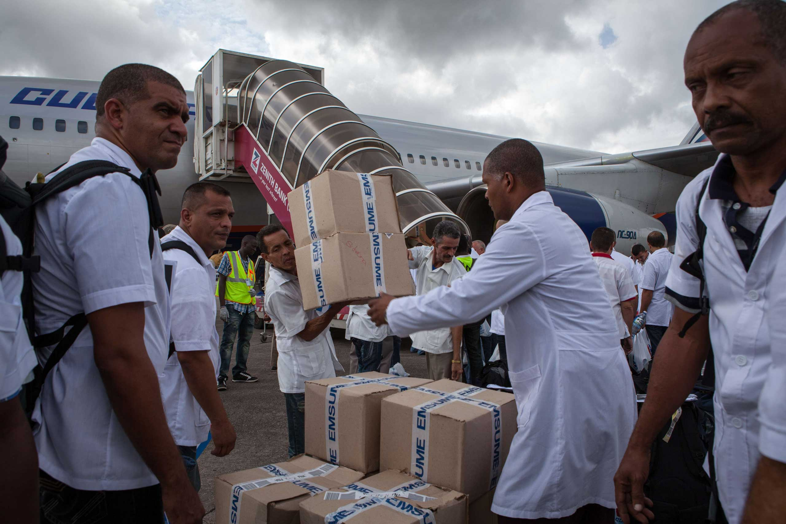 Cuban doctors and health workers unload boxes of medicines and medical material from a plane upon their arrival at Freetown's airport to help the fight against Ebola in Sierra Leone, on Oct. 2, 2014.