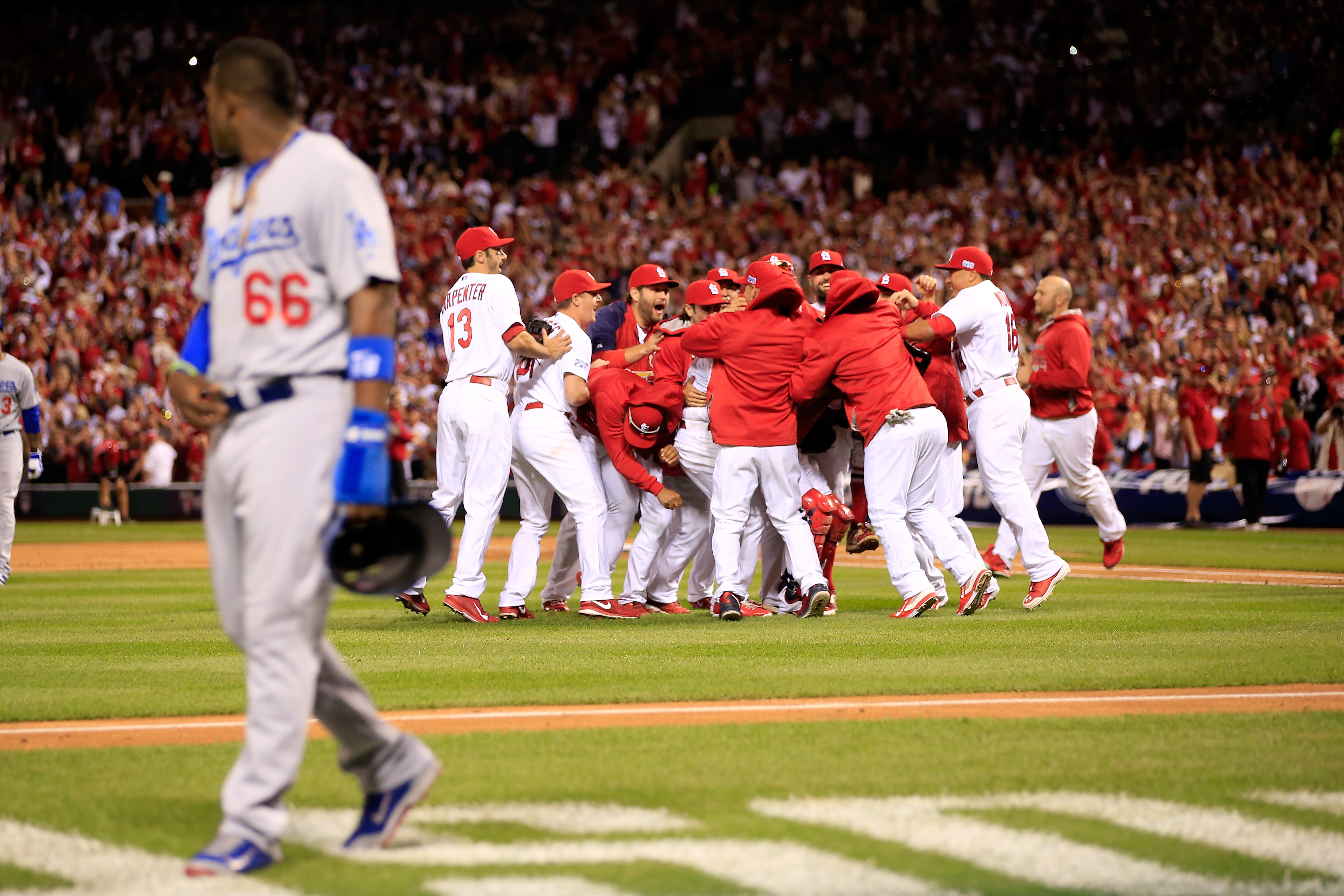 The St. Louis Cardinals celebrate after defeating the Los Angeles Dodgers as Yasiel Puig of the Los Angeles Dodgers walks off the field in Game Four of the National League Divison Series at Busch Stadium on Oct. 7, 2014 in St Louis.