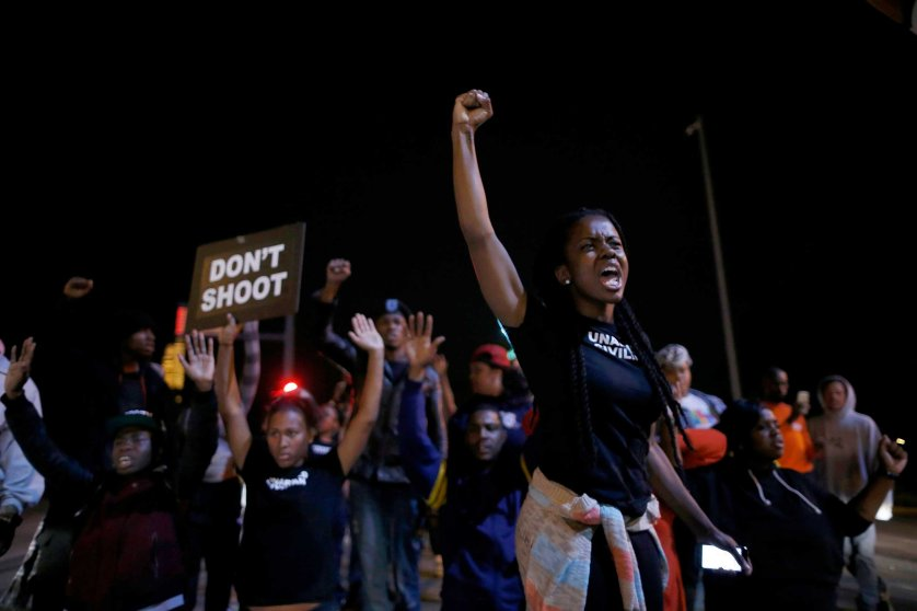 Protesters cheer after blocking an intersection after a vigil in St. Louis