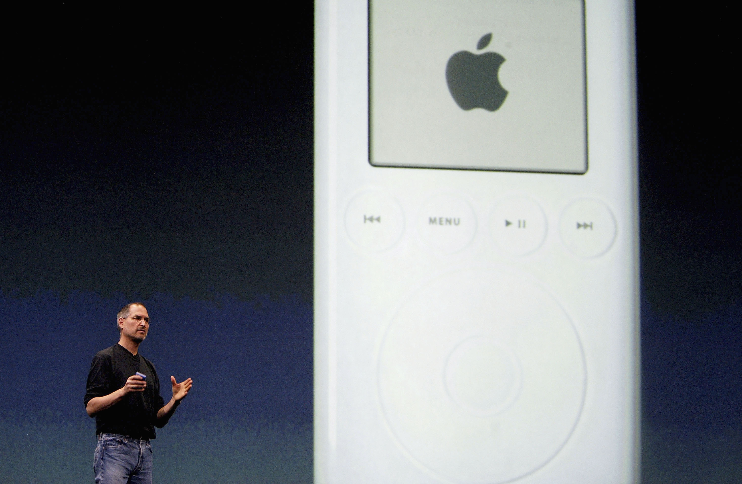 Steve Jobs, Chief Executive Officer of Apple computers, stands by a projection of an iPod as he launches iTunes Music Store in the territories of Great Britain, Germany and France, on June 15, 2004 in London.