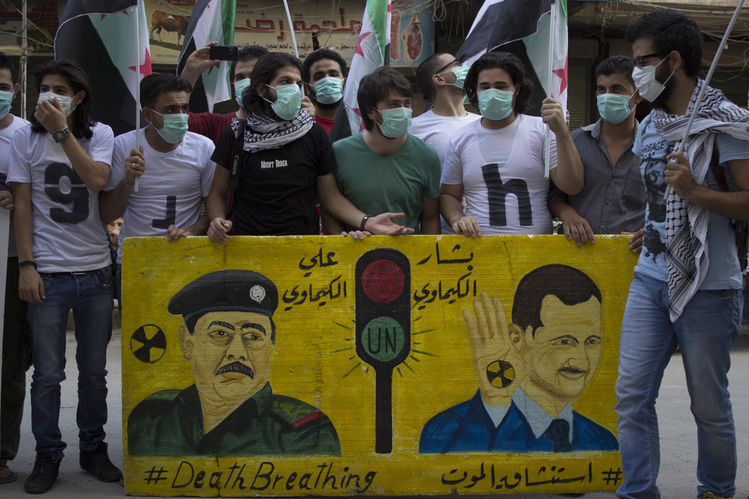 Protesters stand in the first anniversary of the chemical massacre in East Ghota, where hundreds of civilians were killed, in Aleppo, Syria on August 21, 2014.