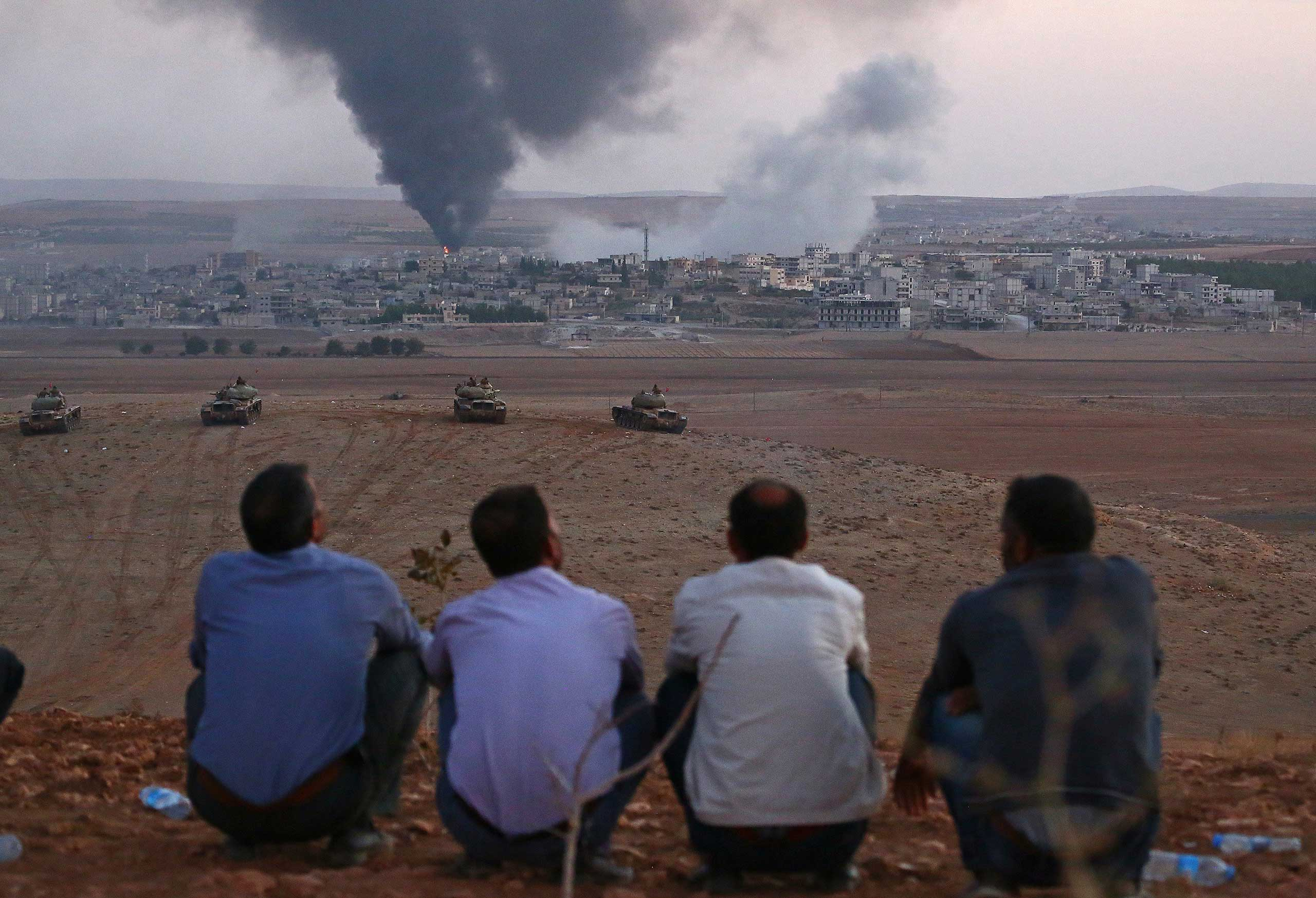Local Turkish residents watch the smoke rising from Syria's Ayn al-Arab city (Kurdish city of Kobani) after clashes between the Islamic State of Iraq and the Levant (ISIS) and Kurdish armed groups in Kobani on Oct. 9, 2014.