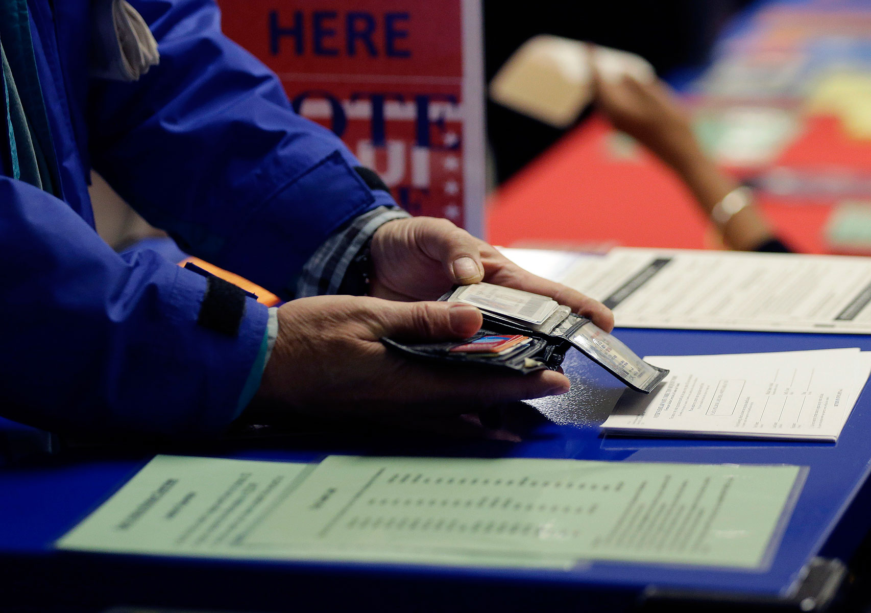 A voter shows his photo identification to an election official at an early voting polling site, in Austin, Texas on Feb. 26, 2014.