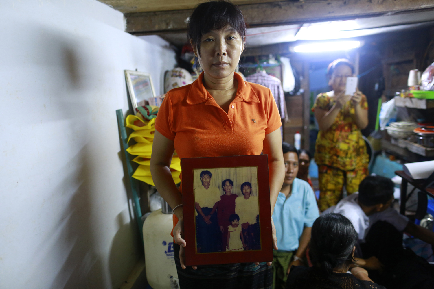 Than Dar, the wife of slain journalist Aung Kyaw Naing, holds a family photograph showing herself, her husband and daughter posing with Aung San Suu Kyi at their home, in Rangoon, on Oct. 28, 2014