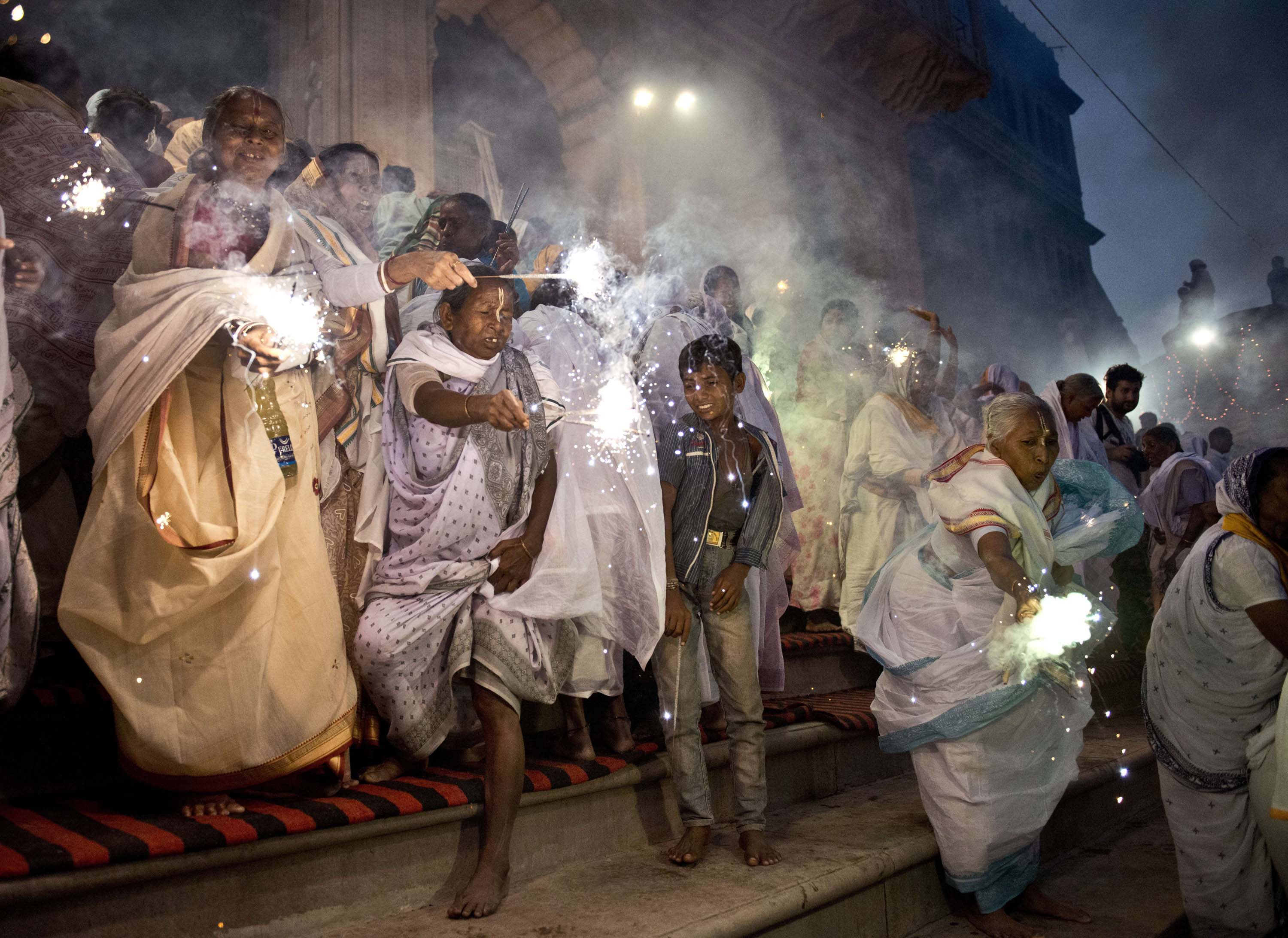 Indian widows wave sparklers as they participate in a celebration for the Hindu festival Diwali on the banks of the Yamuna river in the northern city of Vrindavan on Oct. 21, 2014.