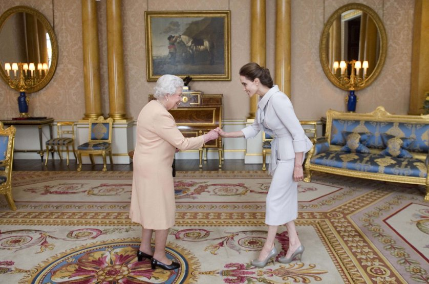 Angelina Jolie is presented with the Insignia of an Honorary Dame Grand Cross of the Most Distinguished Order of St Michael and St George by Britain's Queen Elizabeth II in the 1844 Room at Buckingham Palace in central London, on October 10, 2014.