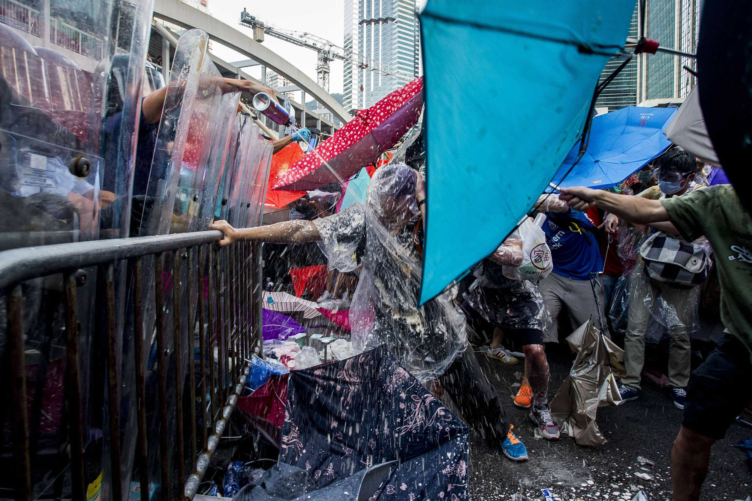 Sept. 28, 2014.                               Pro-democracy demonstrators are sprayed with pepper spray during clashes with police officers during a rally near the Hong Kong government headquarters. Police fired tear gas as tens of thousands of pro-democracy demonstrators brought parts of central Hong Kong to a standstill on September 28, in a dramatic escalation of protests that have gripped the semi-autonomous Chinese city for days.