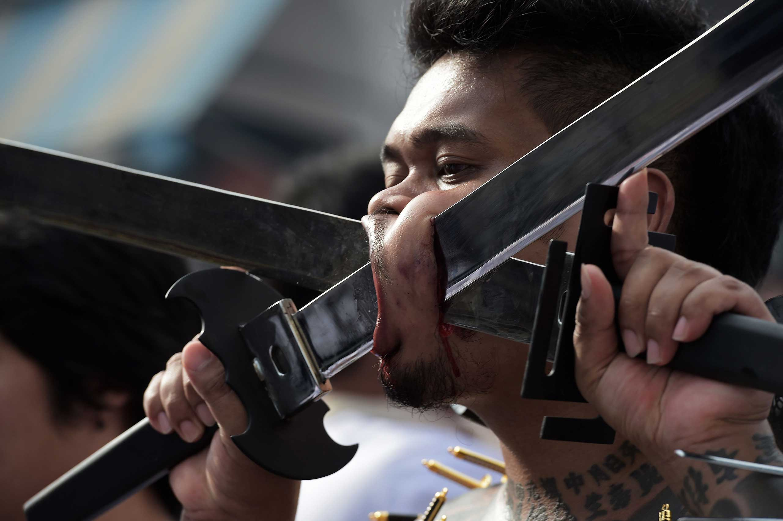 Sept. 29, 2014. A devotee of the Chinese Bang Neow Shrine with swords inserted into his cheeks takes part in a street procession during the annual Vegetarian Festival in the southern Thai town of Phuket. During the festival,  religious devotees slash themselves with swords, pierce their cheeks with sharp objects and commit other painful acts to purify themselves, taking on the sins of the community.