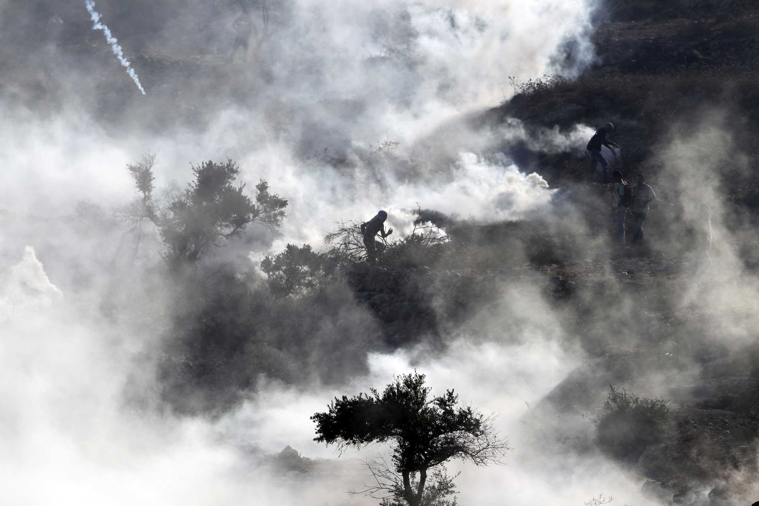 Oct. 17, 2014. Palestinian protesters run amid smoke to take cover after Israeli security forces (unseen) fired tear gas during clashes close to the Israeli Ofer military prison, near the West Bank village of Betunia following a protest after Israeli authorities restricted access to the al-Aqsa mosque compound in Jerusalem. Non-Muslim visits to Al-Aqsa complex are permitted and regulated by police, but Jews are not allowed to pray at the site for fear it could trigger major disturbances.