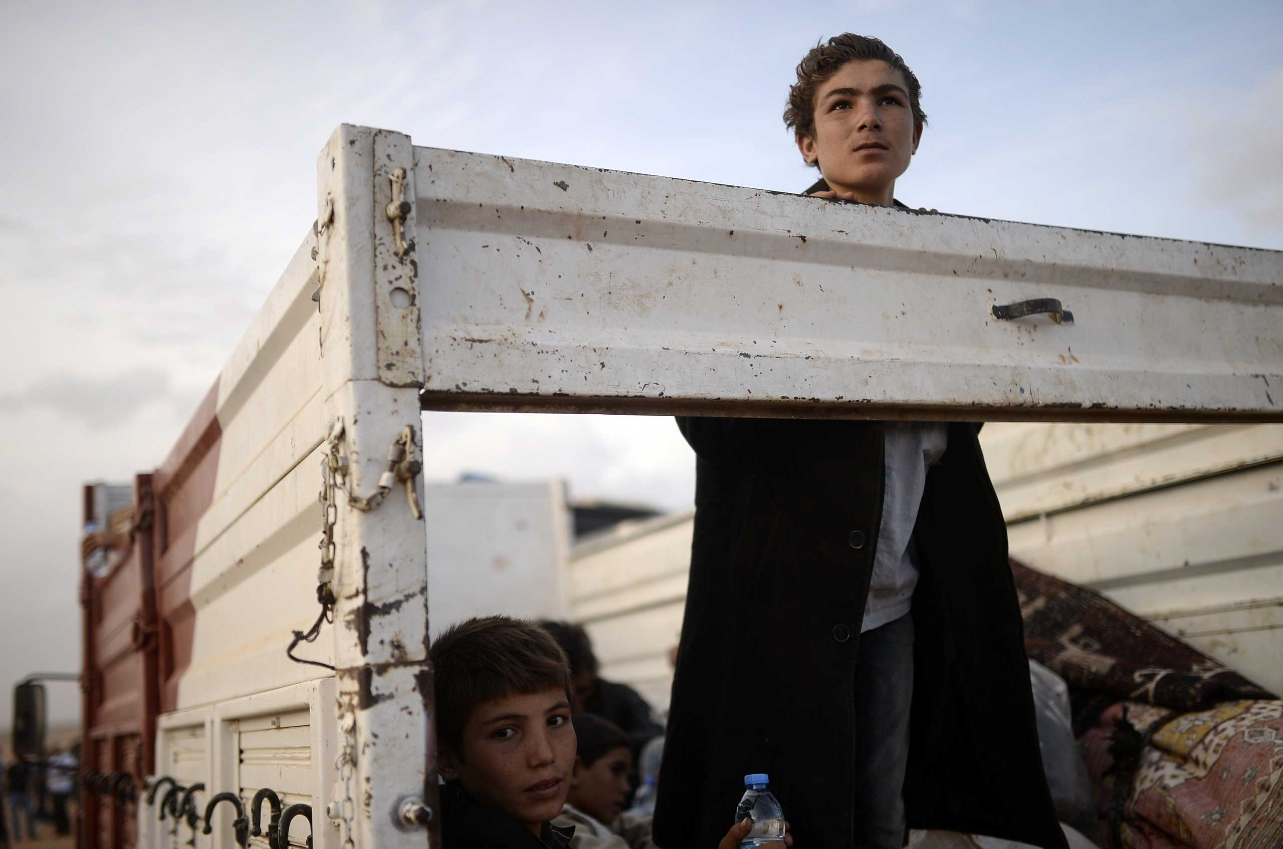 Sept. 27, 2014.                               Syrian Kurdish boys, fleeing an onslaught by the jihadist Islamic State (IS) group, sit in a truck as they cross the border to Turkey at the southeastern town of Suruc in Sanliurfa province.