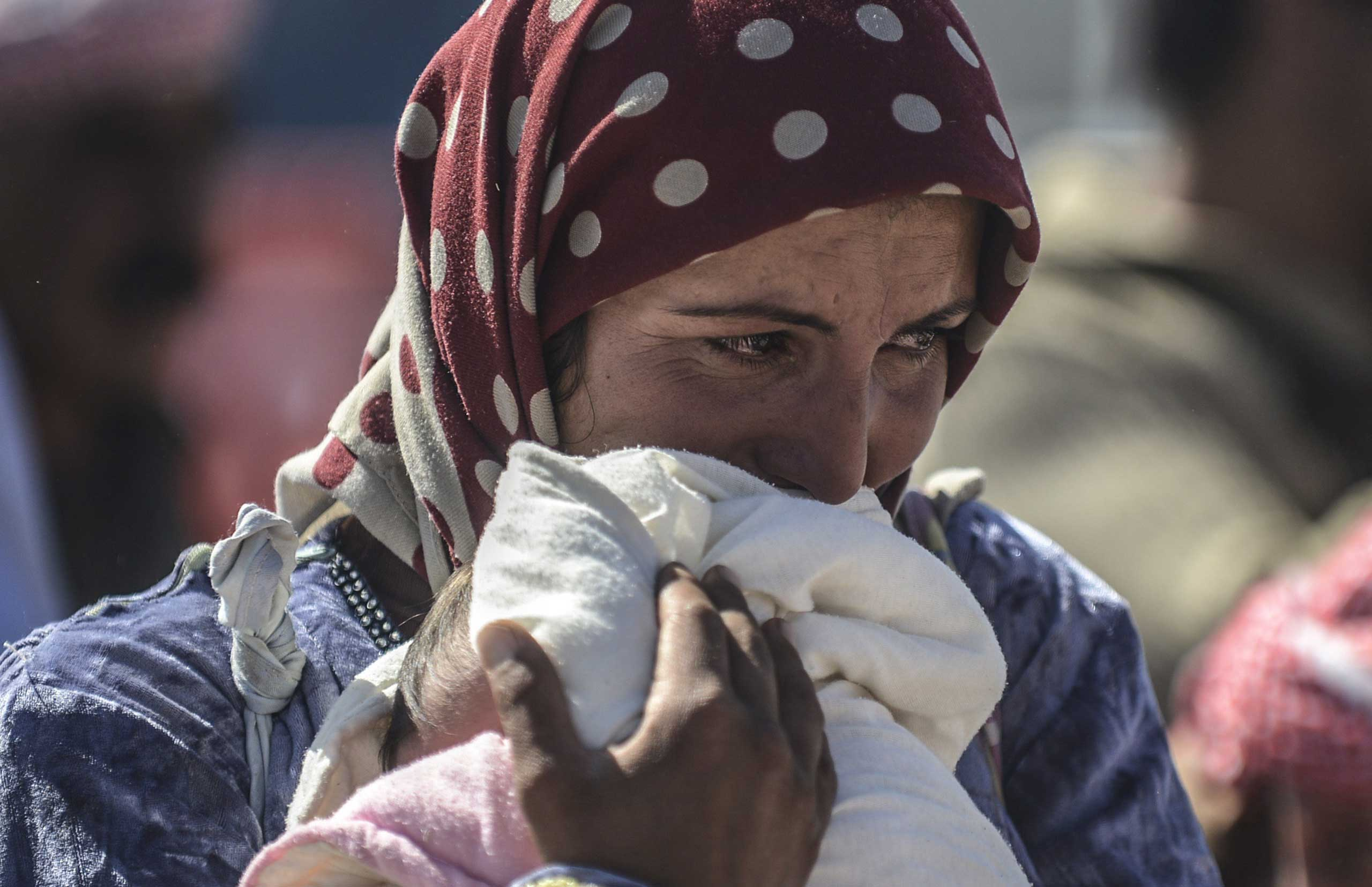Oct. 1, 2014.                               A Syrian Kurdish woman cries as she holds her baby in the southeastern town of Suruc in the Sanliurfa province after crossing the border between Syria and Turkey. Tens of thousands of Syrian Kurds flooded into Turkey fleeing an onslaught by the Islamic State (IS) group that prompted an appeal for international intervention.