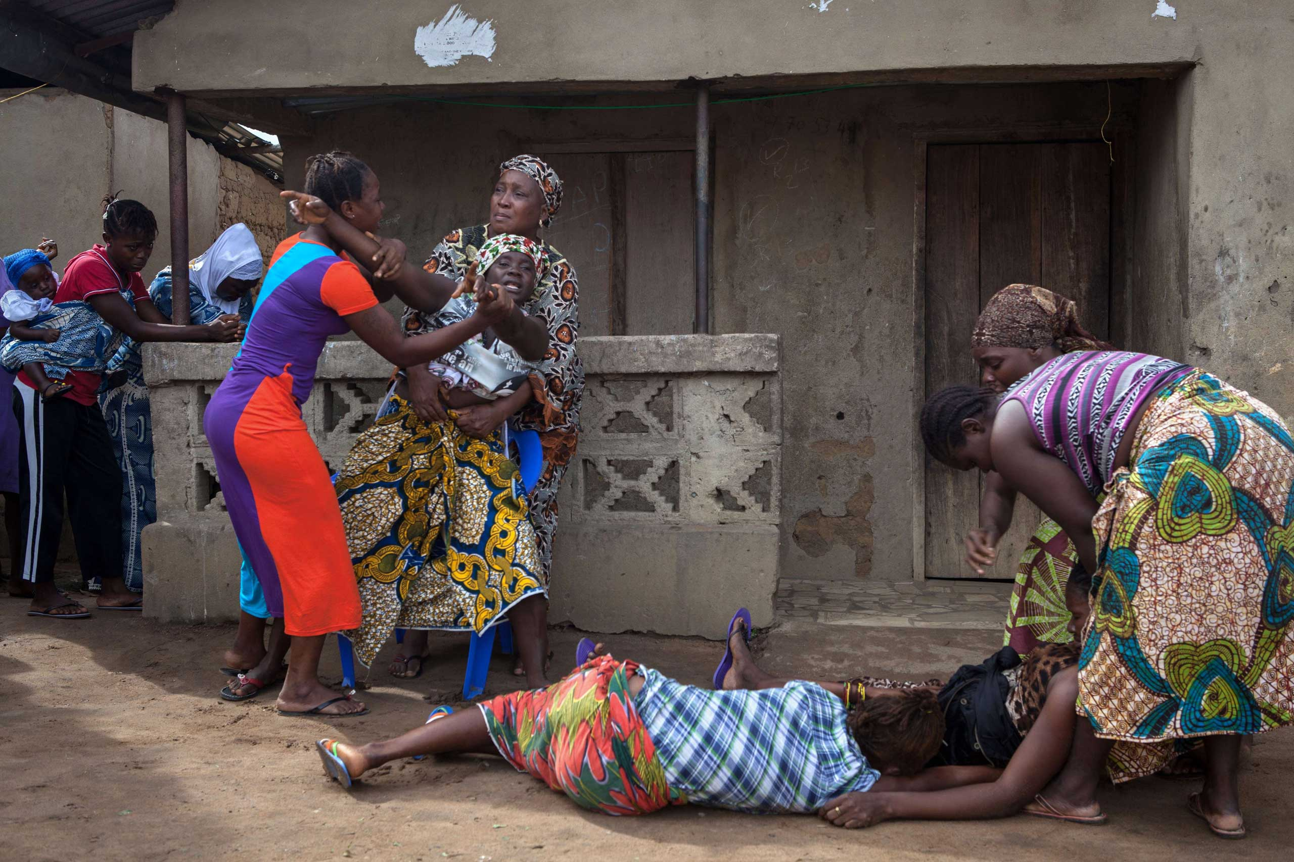 Oct. 7, 2014. Women faint (Bottom) as another reacts while volunteers (unseen) take away from a nearby house the body of a woman who died of Ebola, in Waterloo, some 30 kilometers southeast of Freetown.