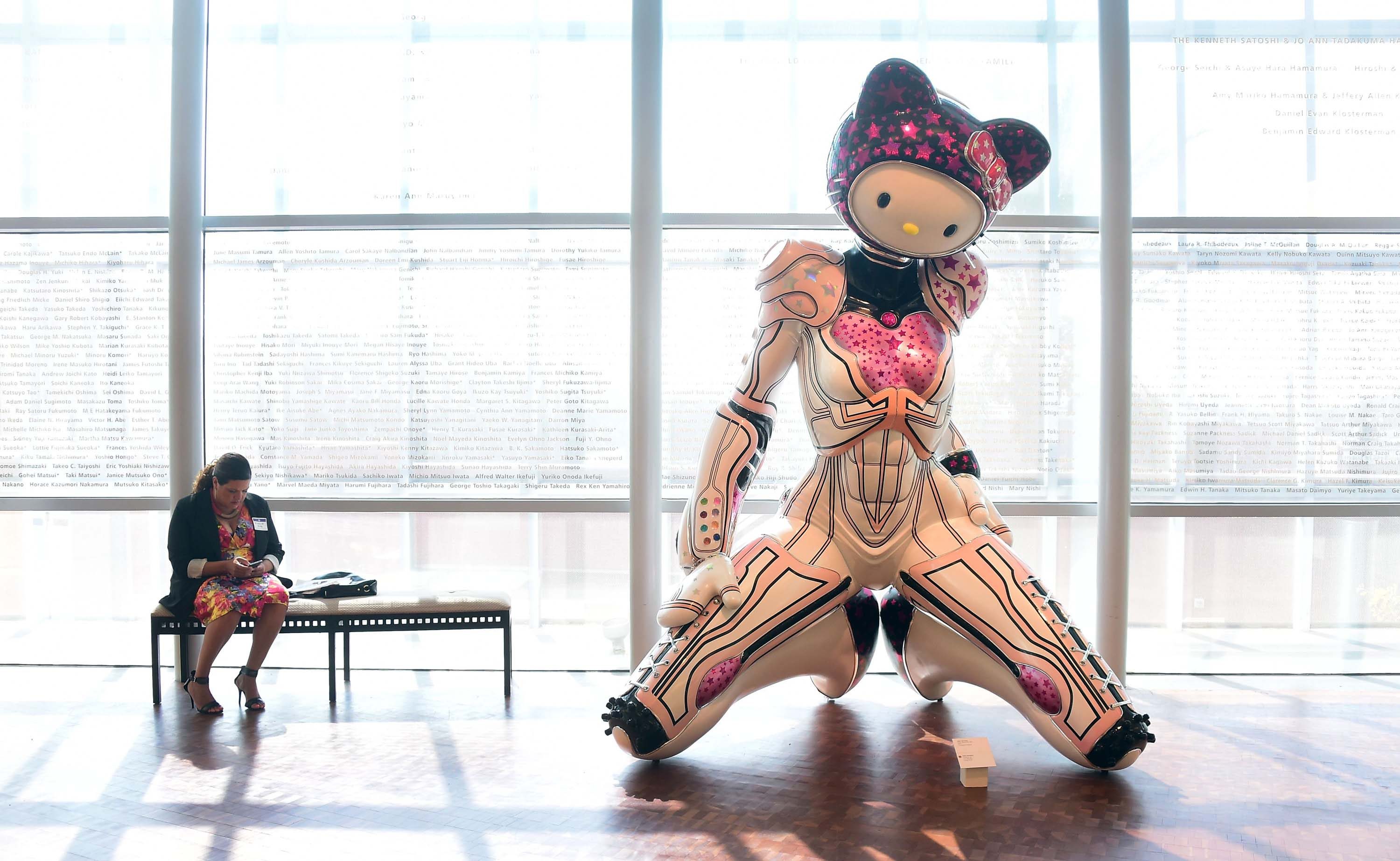 A woman is seated beside a display of  Super Space Titan Kitty , a 2014 fiberglass sculpture by Colin Christian displayed at a press event ahead of the opening of the first ever Hello Kitty exhibition in North America at the Japanese American National Museum in Los Angeles on Oct. 10, 2014.