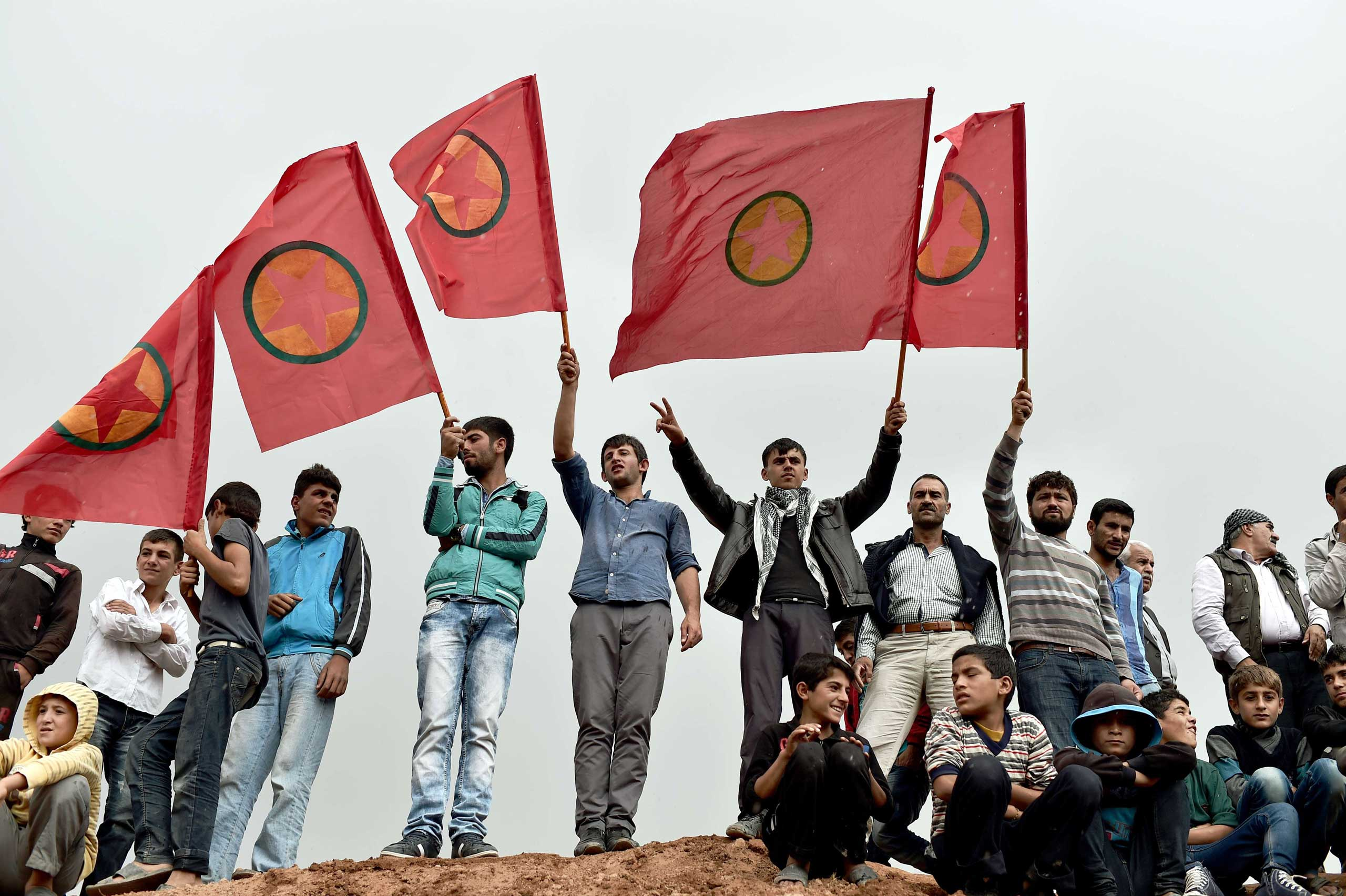 Kurdish people wave Kurdistan Workers' Party (PKK) flags while attending a funeral ceremony for YPG (People's Protection Units) fighters in the town of Suruc, Sanliurfa province, on Oct. 14, 2014.