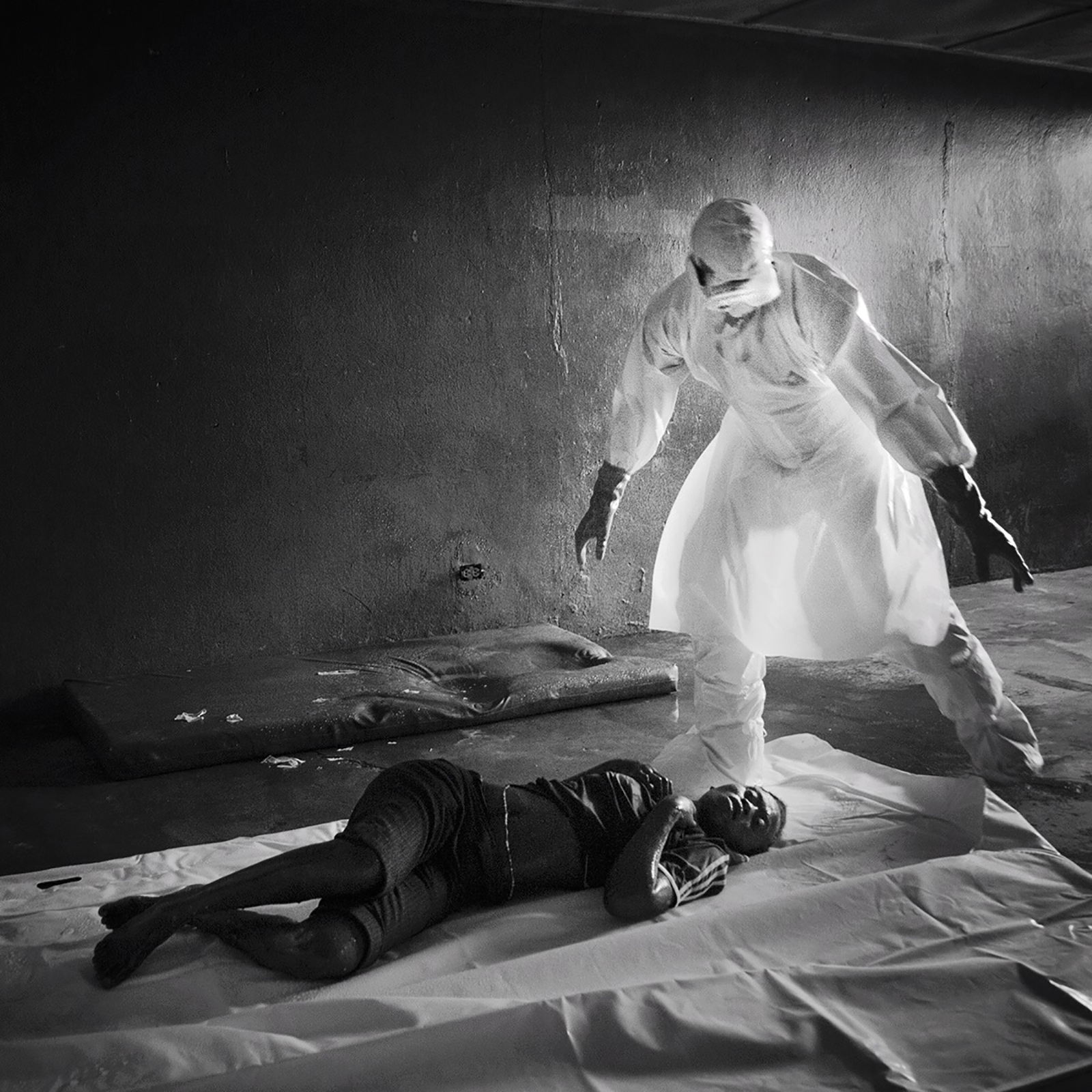 """<b>Kieran Kesner, Aug. 28, 2014. Monrovia, Liberia.</b>                                                                      """"This is a photograph of the first person I saw who had died from the Ebola virus in West Point, Monrovia. After the  Liberian government mandated all schools be shut down in an attempt to stop the spread of the virus, the empty rooms of this school were converted into a temporary Ebola holding center. I entered the building alone and photographed the woman from a distance. I began to make my way closer to her, being careful to avoid the puddles of vomit and other pools of still liquid on the cement floor. Standing over her, I noticed the unbroken beads of sweat that remained on her face and realized the woman had only died a few hours before. I took a few steps back as a body removal team entered the room. Up until this point, to me, Ebola deaths seemed like statistics, but suddenly it had become real. I became enveloped in fear: fear of the invisible killer in the room, fear that I might have made a mistake, fear that I wouldn't know for days whether or not I was sick, and fear that I would infect my family and loved ones.  I desperately wanted to leave the room, to leave the country, to be home, but I couldn't. I continued to photograph. I watched as the men burdened with the task of removing her body, clad all in angel white, lifted the woman from her mattress and placed her in a body bag on the floor. I photographed as they sprayed her one last time with disinfectant and zipped it shut."""""""