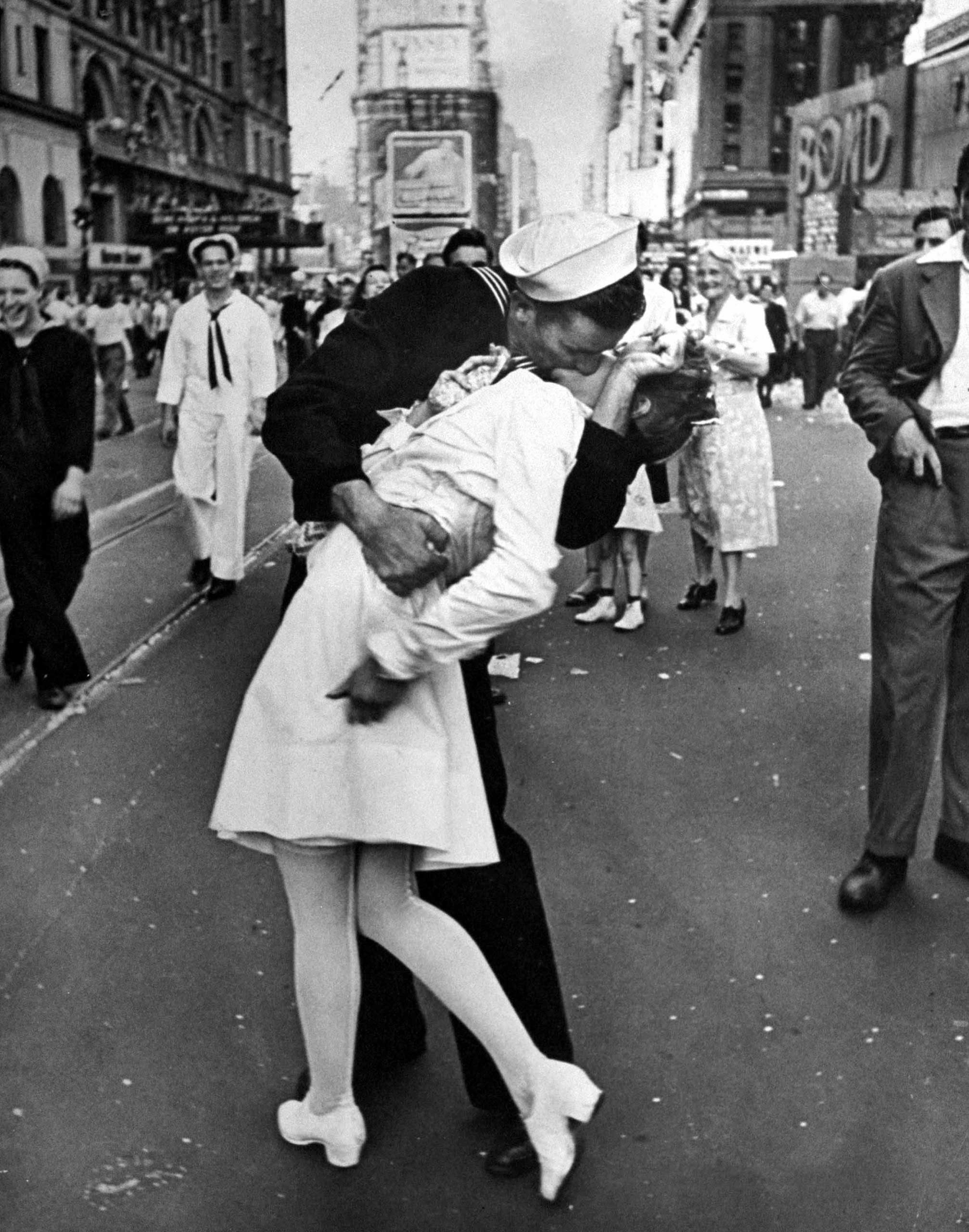 Caption from the Aug. 27, 1945, issue of LIFE.  In the middle of New York's Times Square a white-clad girl clutches her purse and skirt as an uninhibited sailor plants his lips squarely on hers.