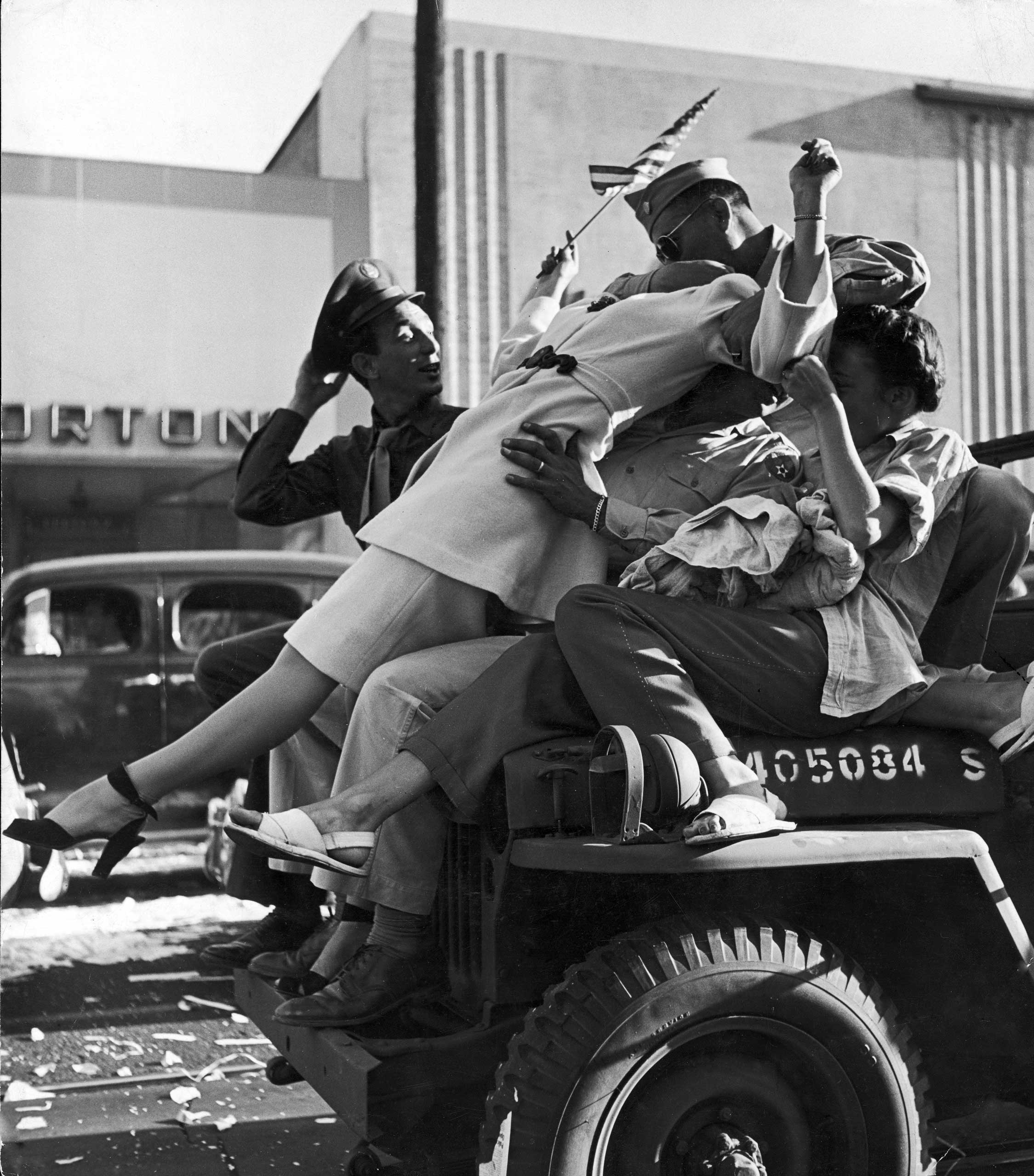 Caption from LIFE.  On Hollywood Boulevard in Los Angeles carousing servicemen neck atop the hood of a careening jeep. The city rocked with joy as impromptu pedestrian parades and motor cavalcades whirled along, hindered only by hurled whiskey bottles, amorous drunks and collisions.