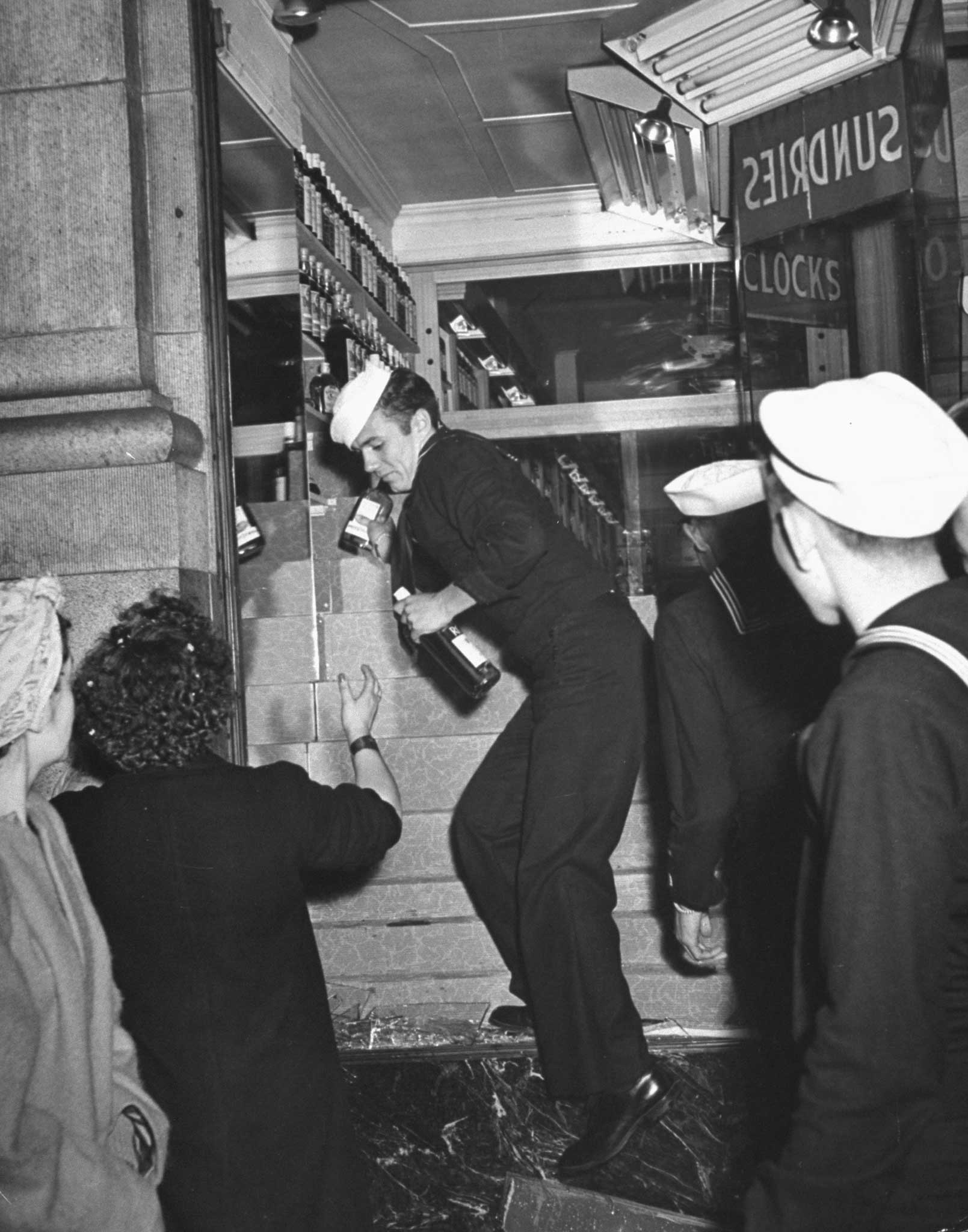 Caption from LIFE.  In San Francisco sailors break into a liquor store and pilfer the stock. Revel turned into a riot as tense servicemen, reprieved from impending Pacific war-zone duty, defaced statues, over-turned street cars, ripped down bond booths, attacked girls. The toll: 1,000 casualties.