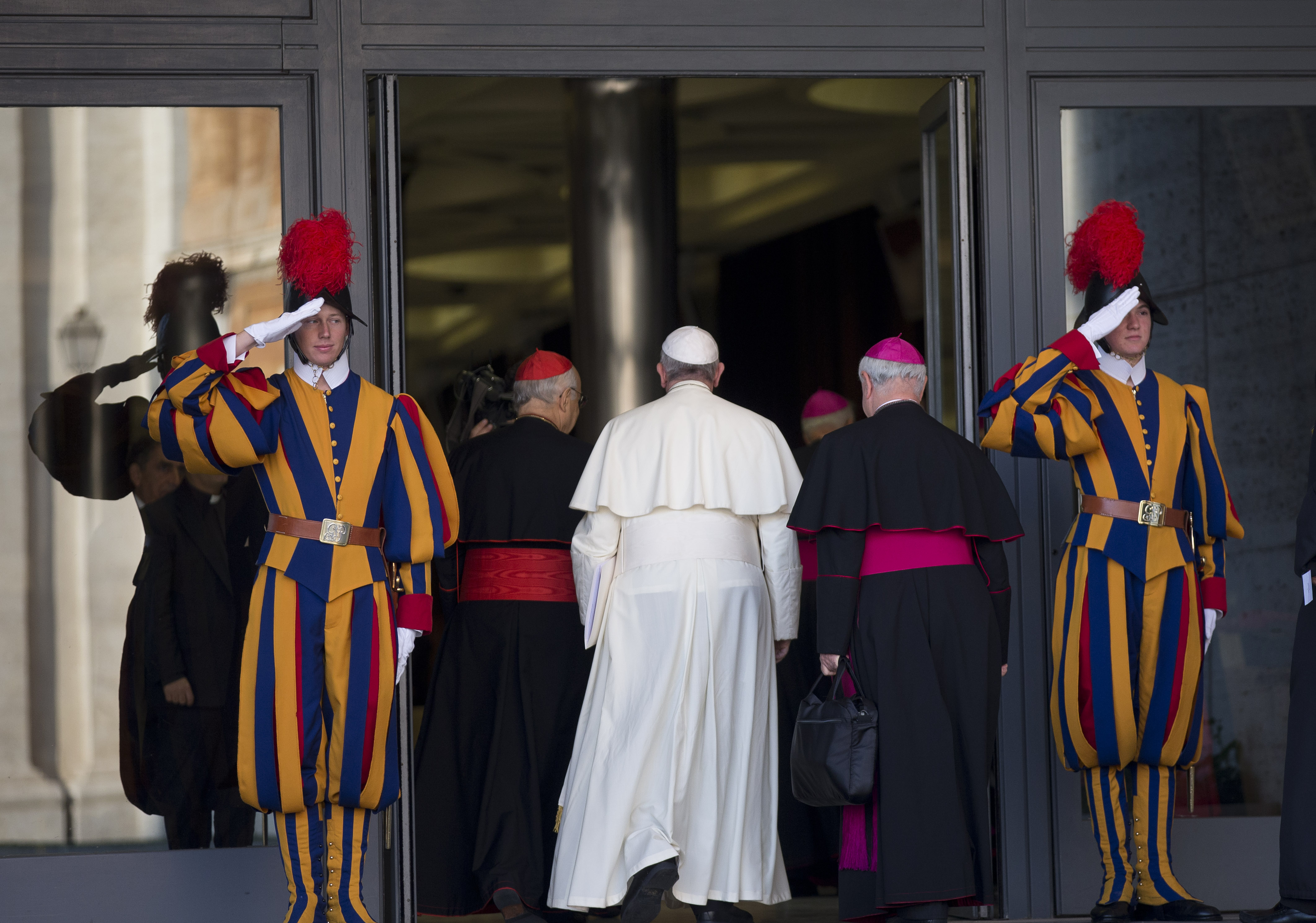 Vatican Swiss Guards stand on salute as Pope Francis arrives for the morning session of a two-week synod on family issues including contraception, pre-marital sex and divorce, at the Vatican, Oct. 6, 2014.