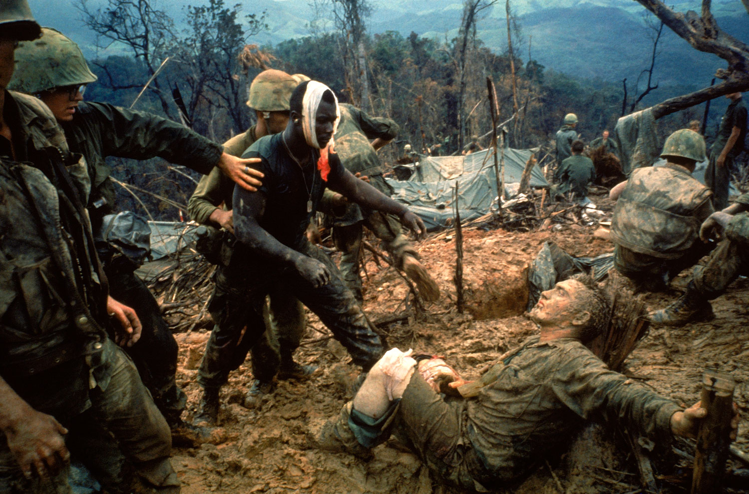 Wounded Marine Gunnery Sgt. Jeremiah Purdie (center, with bandaged head) reaches toward a stricken comrade after a fierce firefight south of the DMZ, Vietnam, October 1966.