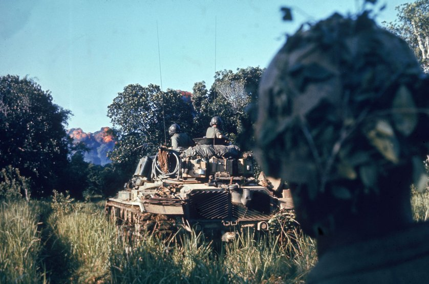 """Escorted by tanks and supported by air strikes that sear the jungle just ahead, troops of the Second Battalion, Fifth Marines, begin a sweep."" Vietnam, October 1966."