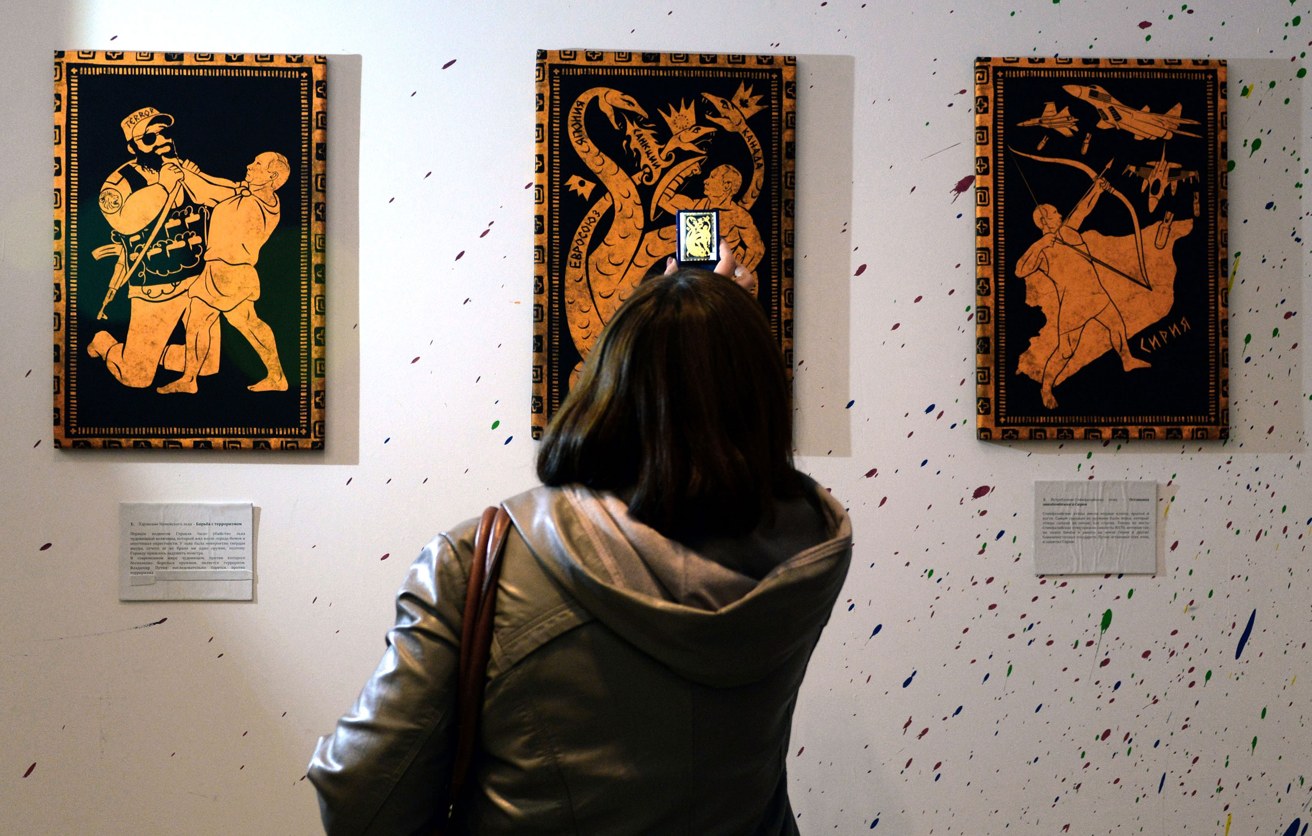 A visitor takes photos of the paintings during the  12 Labours of Putin  art exhibition on Oct. 6, 2014 marking the 60th birthday of Russia's President Vladimir Putin at the design workshop in Moscow.