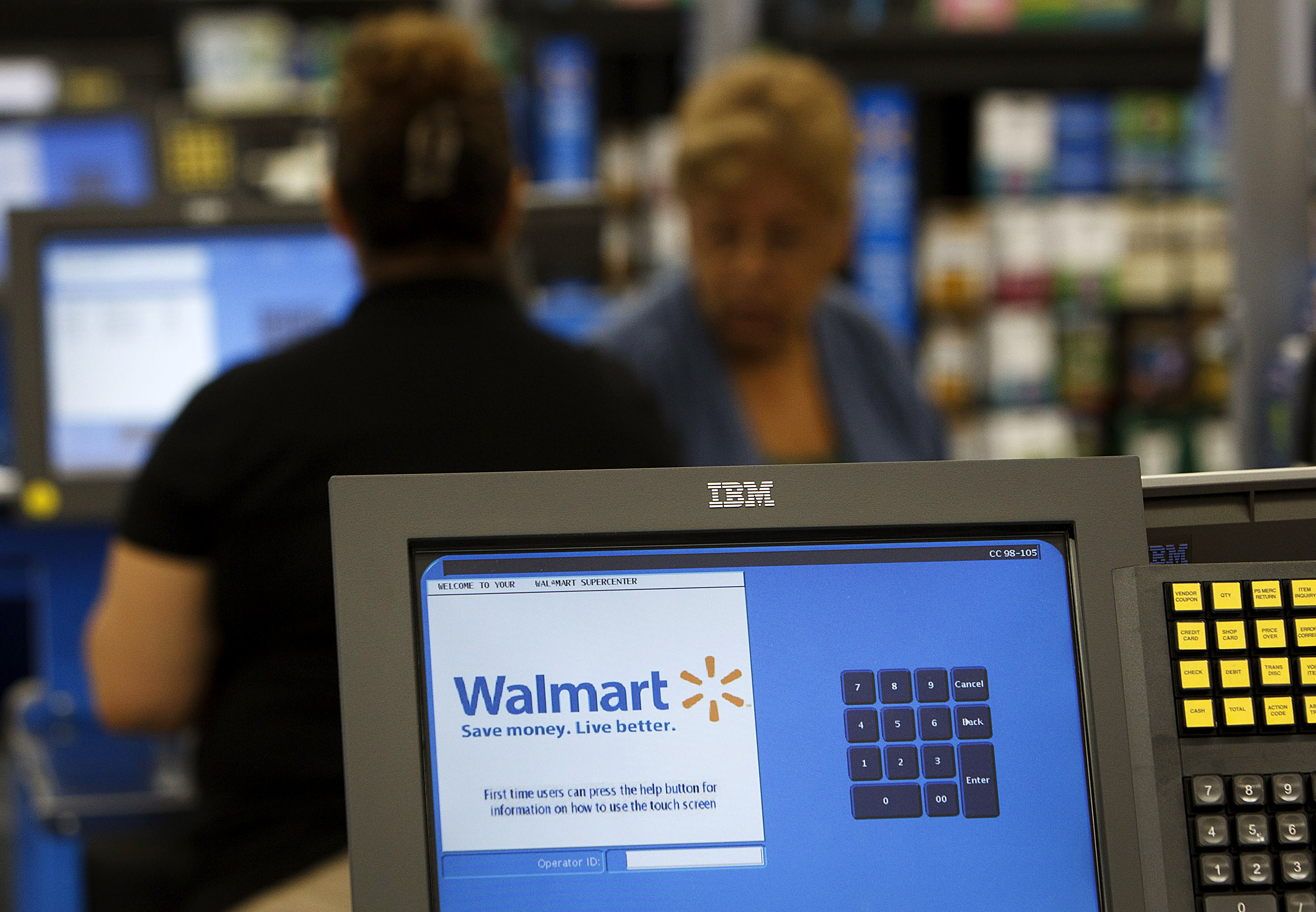 Wal-Mart Stores Inc. signage is displayed on a check out register during the grand opening of a new location in Torrance, California, U.S., on Wednesday, Sept. 12, 2012.