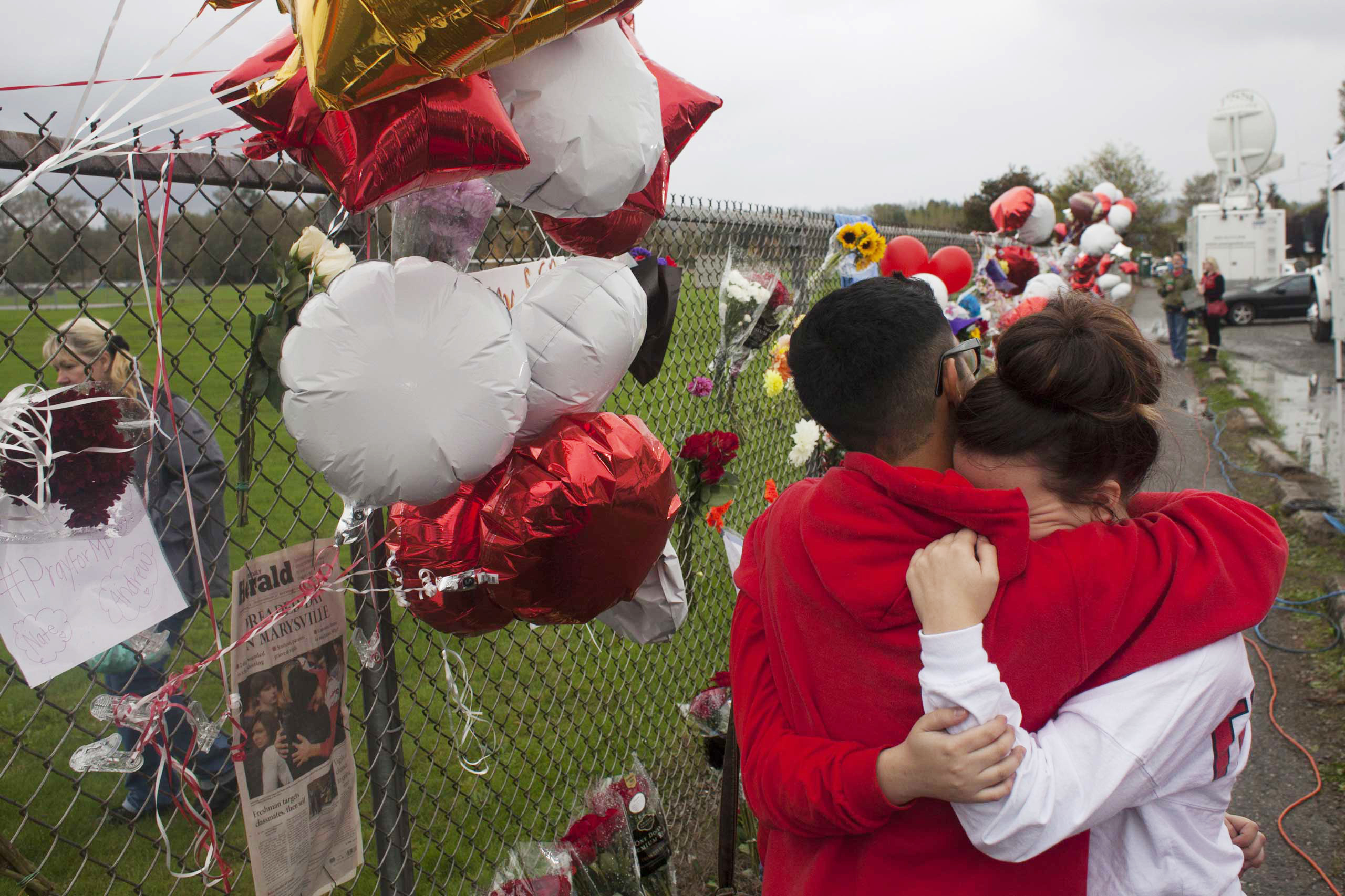 Students grieve beside a makeshift memorial at Marysville-Pilchuck High School in Marysville, Wash.