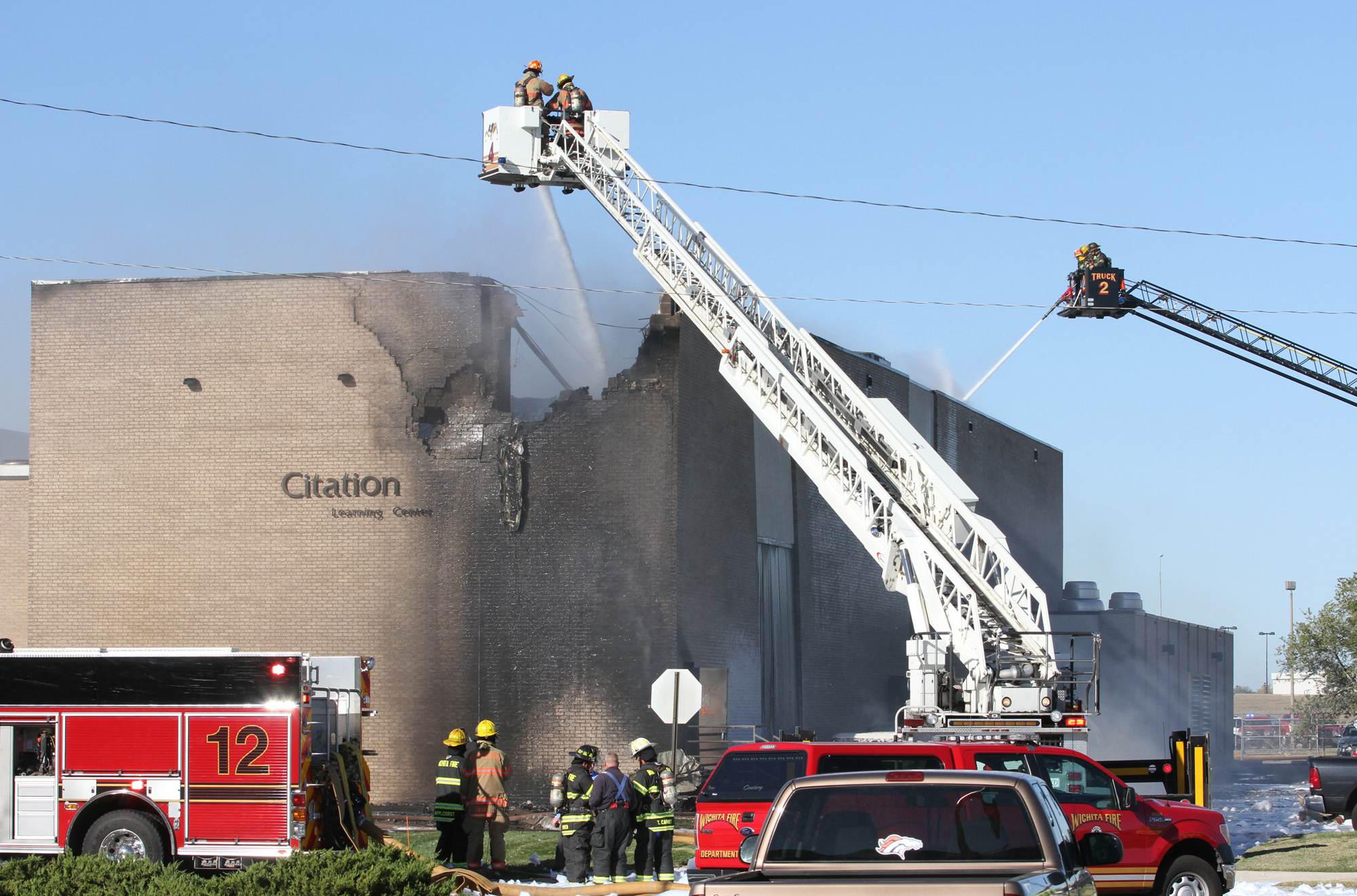 Firefighters try to put out a fire at Mid-Continent Airport in Wichita, Kan. on Oct. 30, 2014 shortly after a small plane crashed into the building killing several people including the pilot.