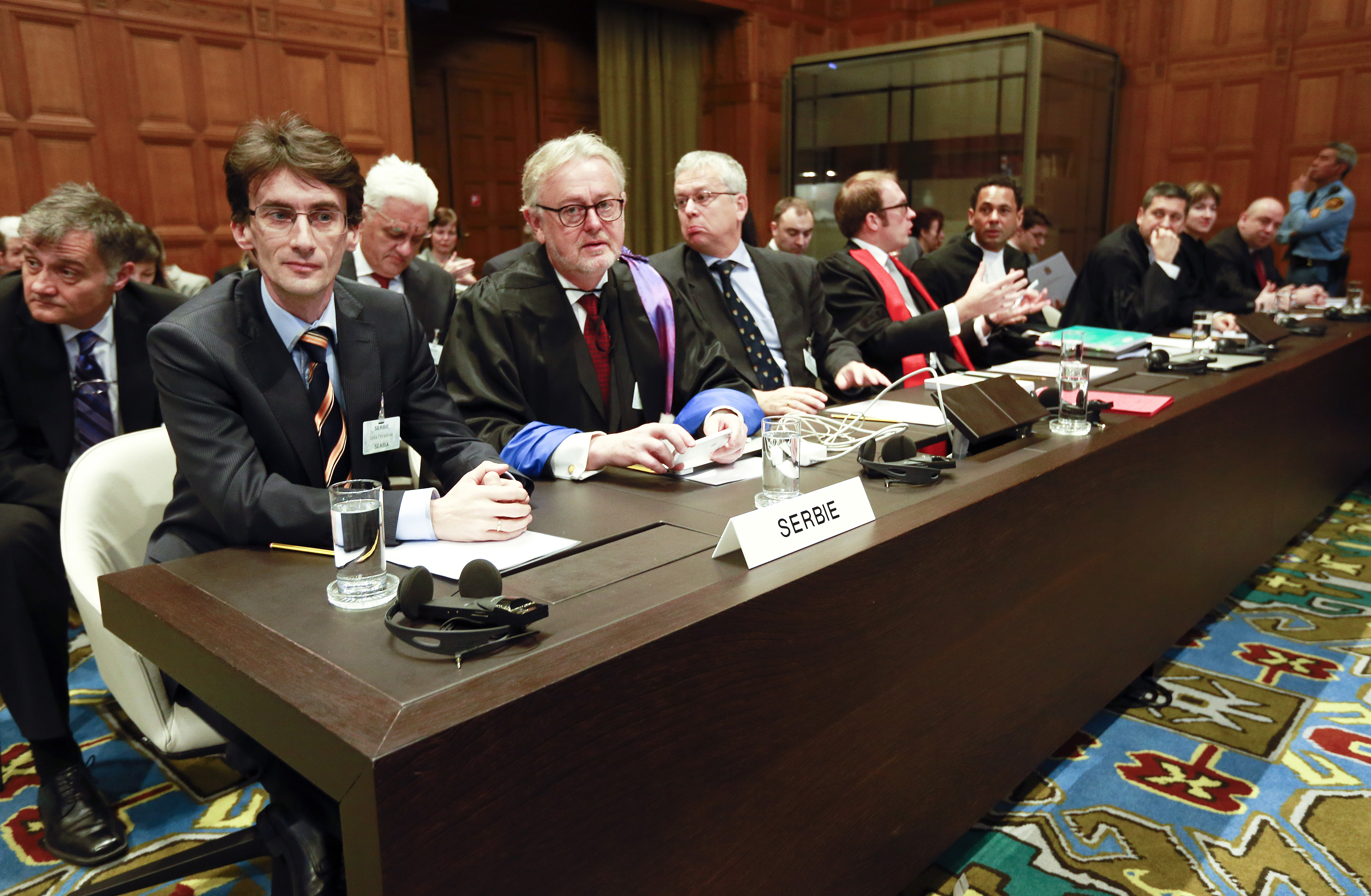 Members of the Serbian delegation, from left: Sasa Orbadovic, William Schabas, Andreas Zimmermann, Christian Tams and Wayne Jordash await the start of public hearings at the International Court of Justice (ICJ) in The Hague,  Netherlands, Monday, March 3, 2014.