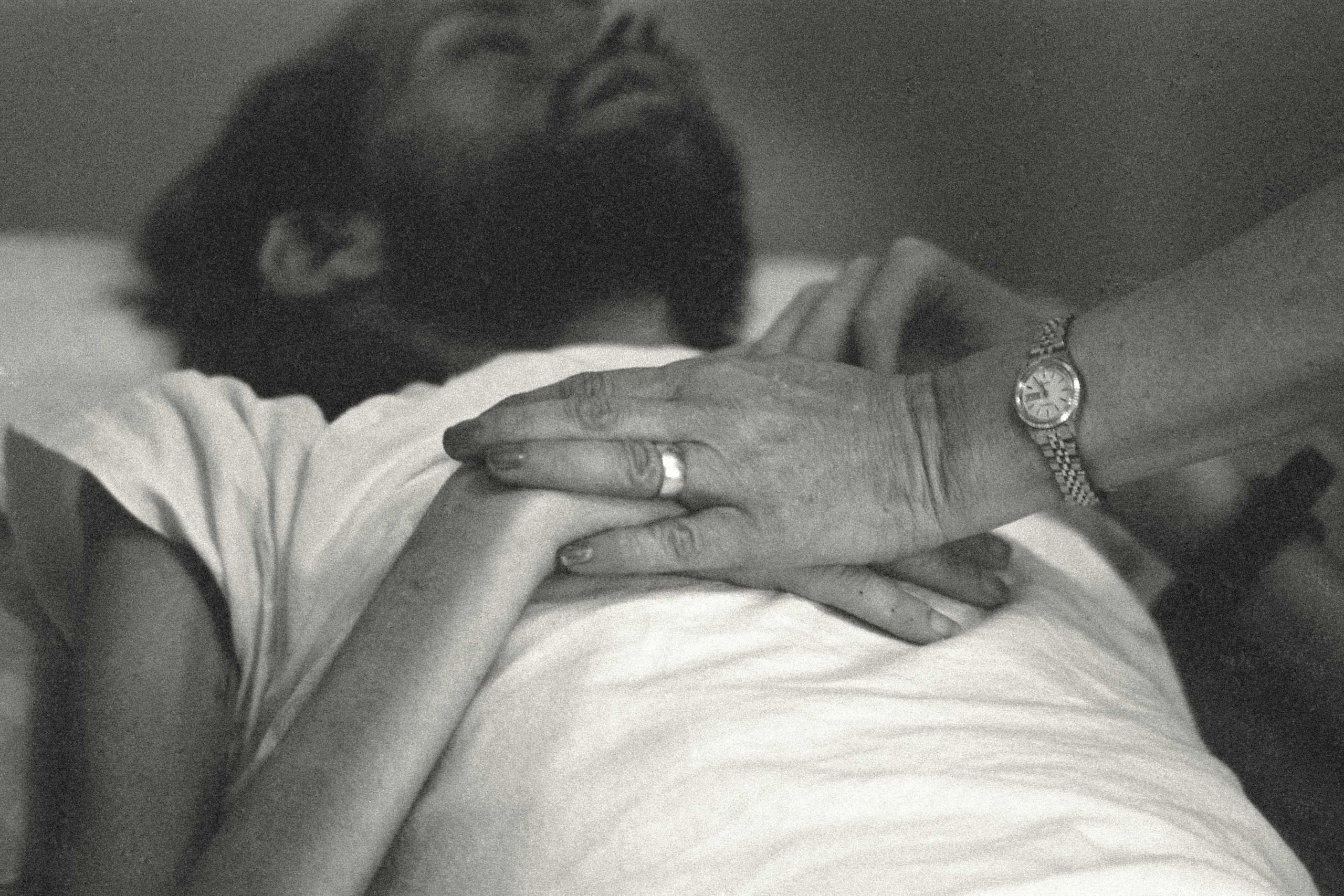 A nurse at Pater Noster House in Ohio holds David Kirby's hands not long before he died, spring 1990.