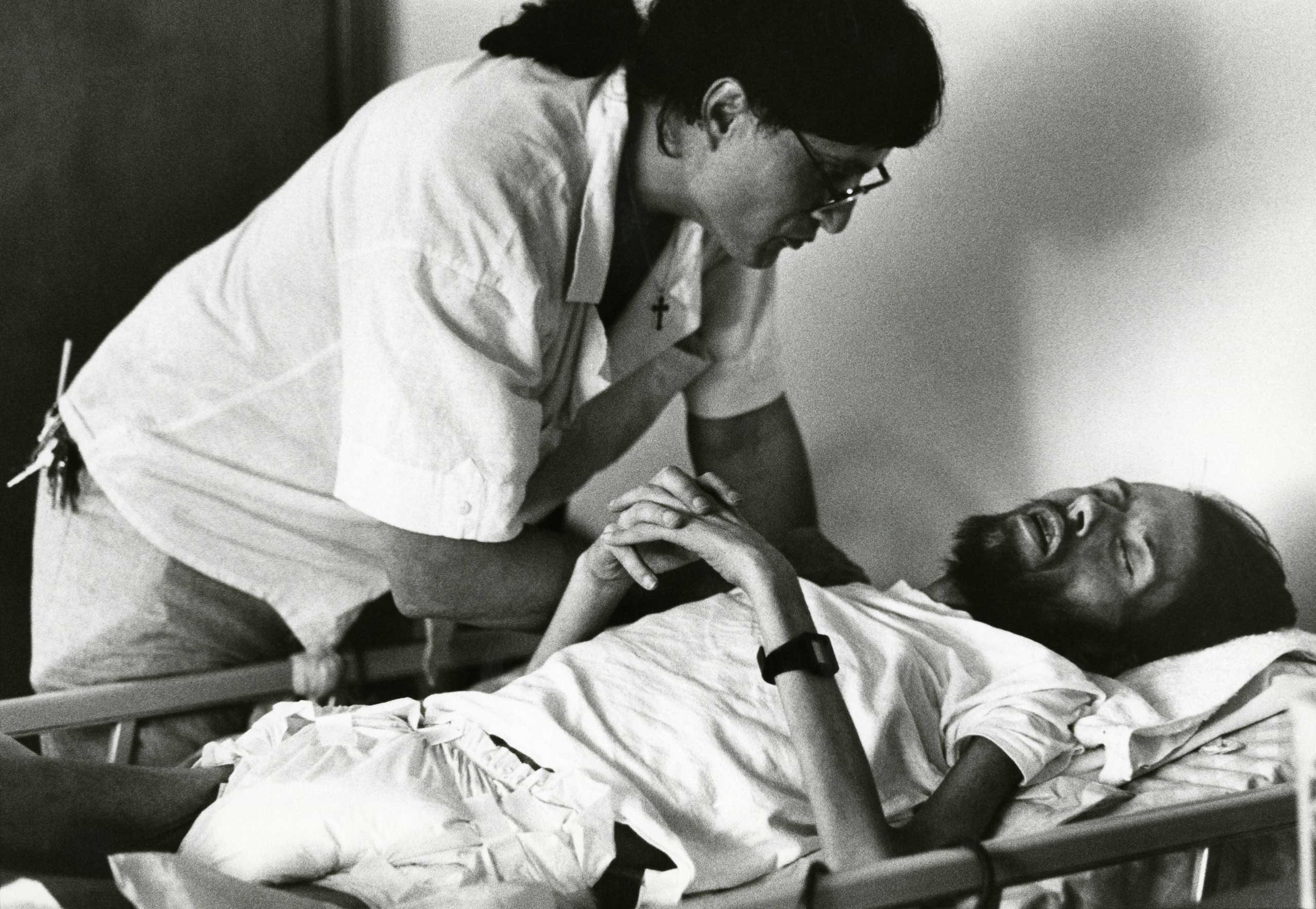Peta, a volunteer at Pater Noster House in Ohio, cares for a dying David Kirby, 1990.