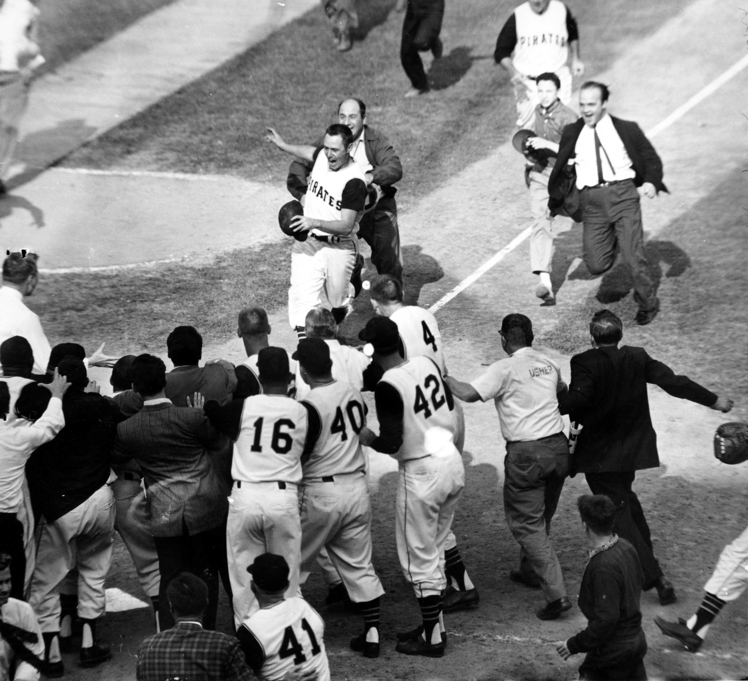 Fans rush onto the field toward Pittsburgh Pirates second baseman Bill Mazeroski as he comes home on his ninth-inning home run to win the World Series in Pittsburgh, Pa. on Oct. 13, 1960.