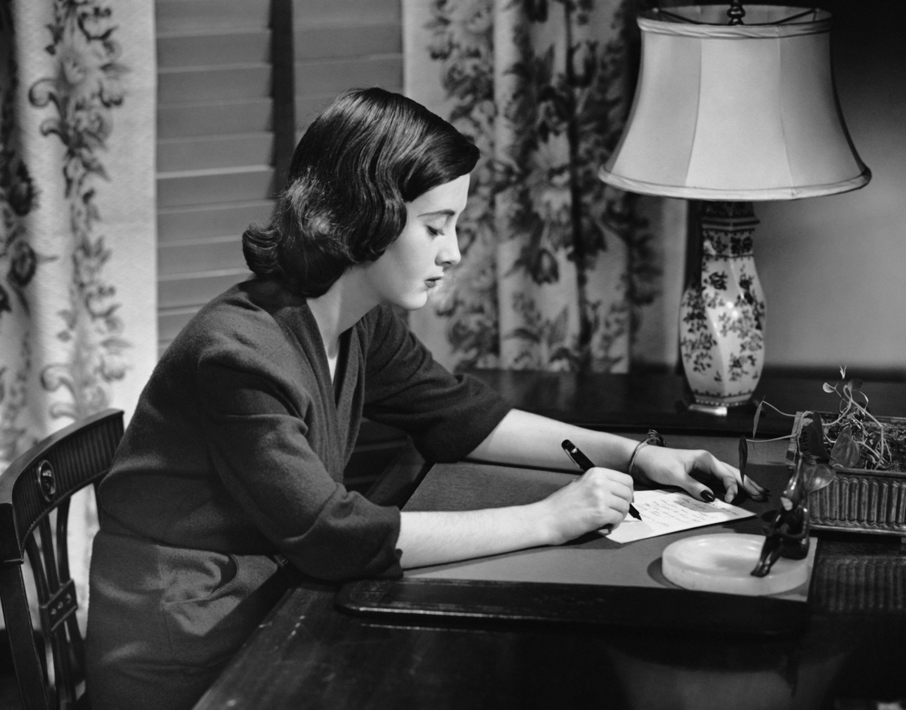 Portrait of woman writing letter at desk, circa 1950