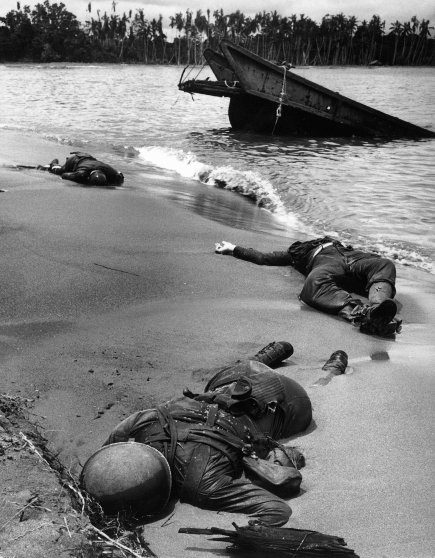 """Three dead Americans on the beach at Buna."""