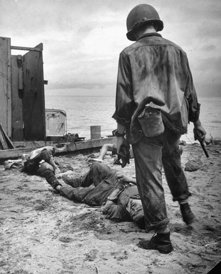 """An American soldier stands over a dying Jap whom he has just been forced to shoot. The Jap had been hiding in the landing barge, shooting at U.S. troops."" New Guinea Campaign, 1942."