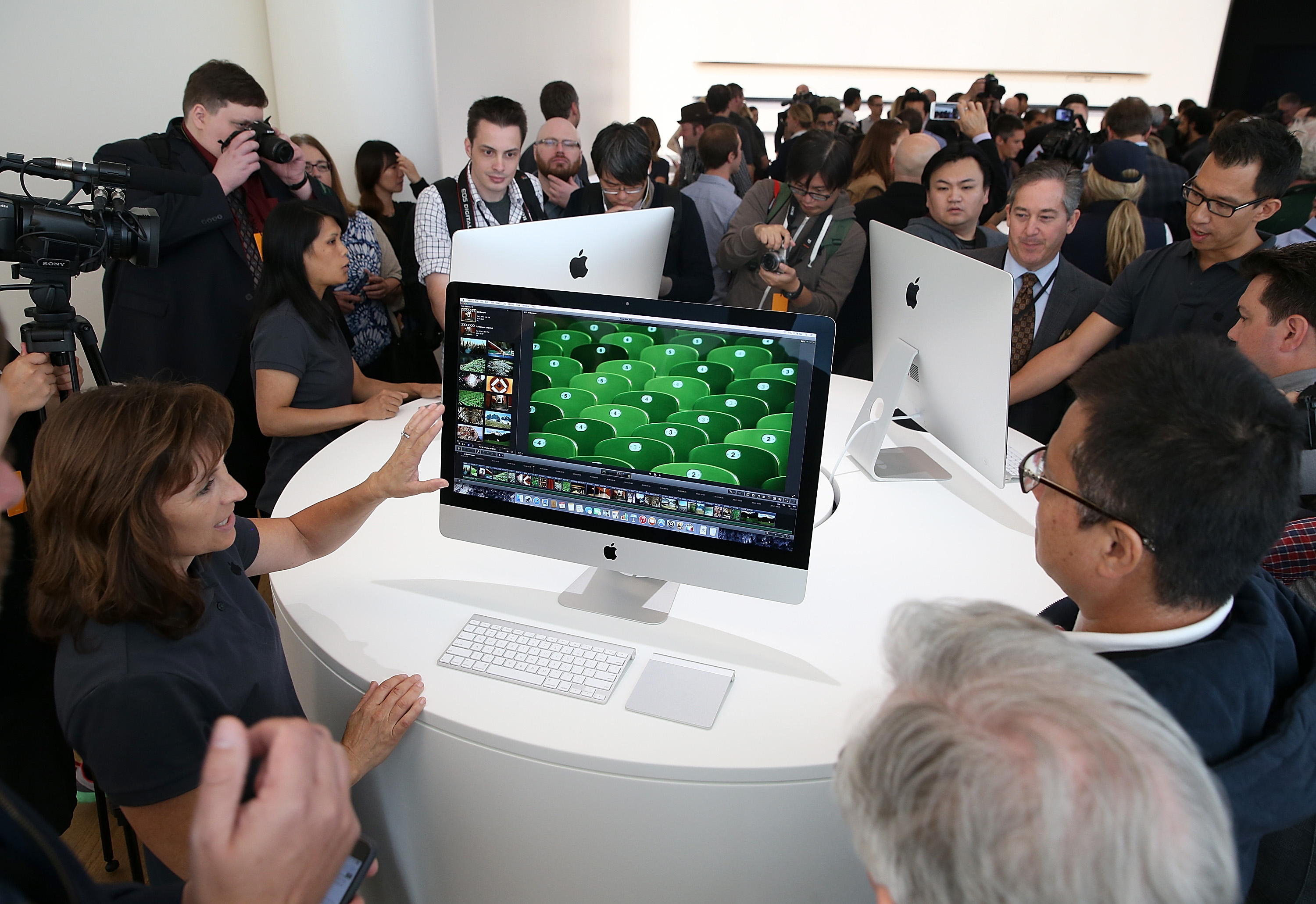 Attendees inspect the new 27 inch iMac with 5K Retina display during an Apple special event on October 16, 2014 in Cupertino, California.